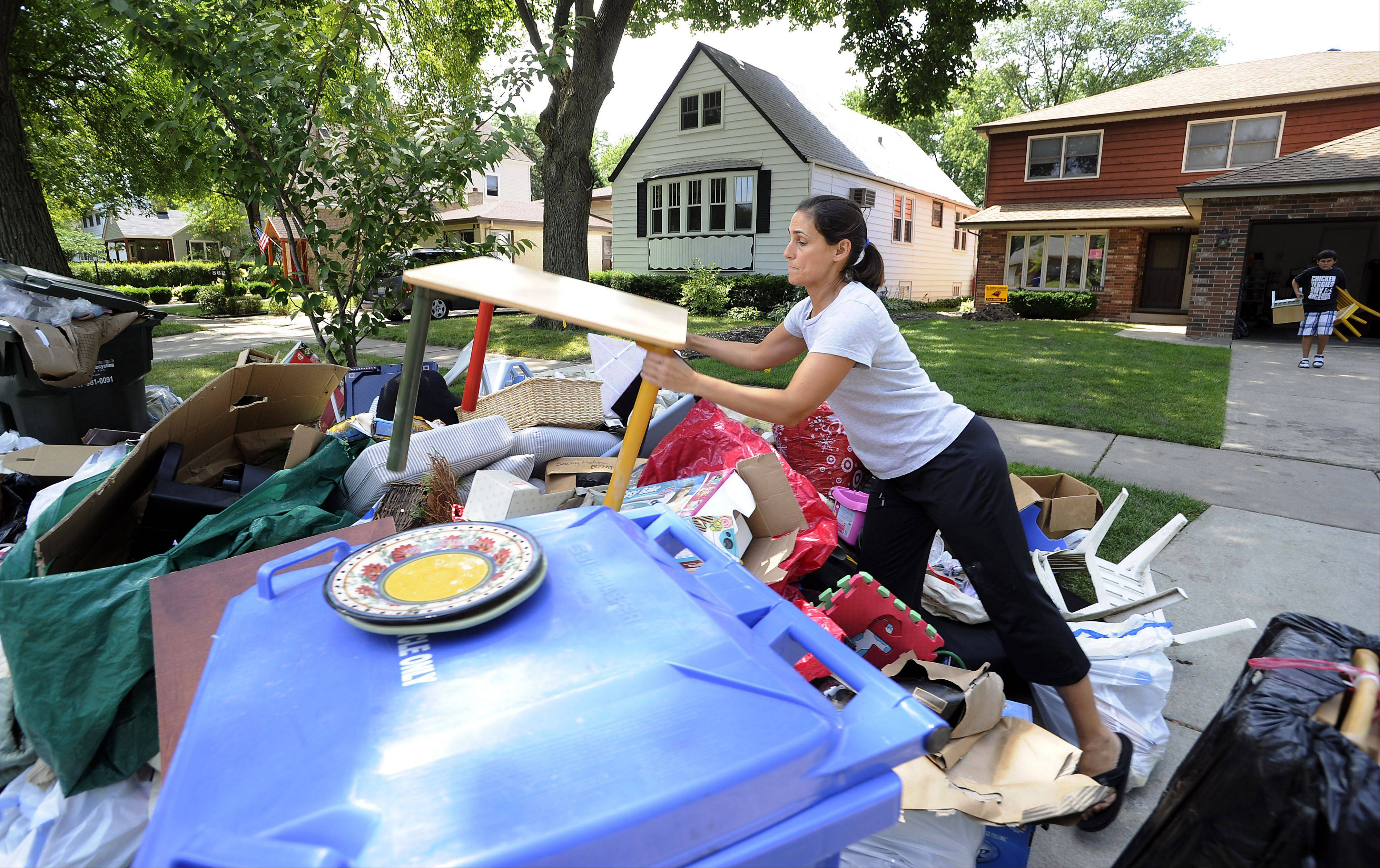 Jackie Mirza of Des Plaines throws a kids table and chair atop the huge pile of trash in front of her house. It all came out of her basement.