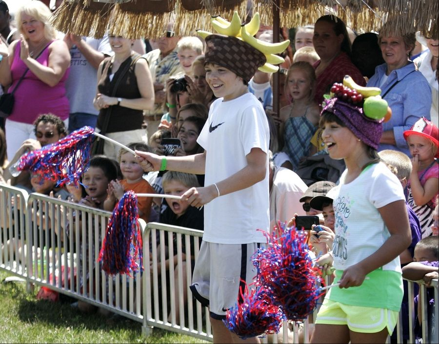 "Ryan Donnelly, 13, of Grayslake, left and Olivia Coutre, 10, of Mundelein act as cheerleaders during the Banana Derby with ""America's Favorite Monkey Jockeys"" Tuesday at the Lake County Fair in Grayslake."