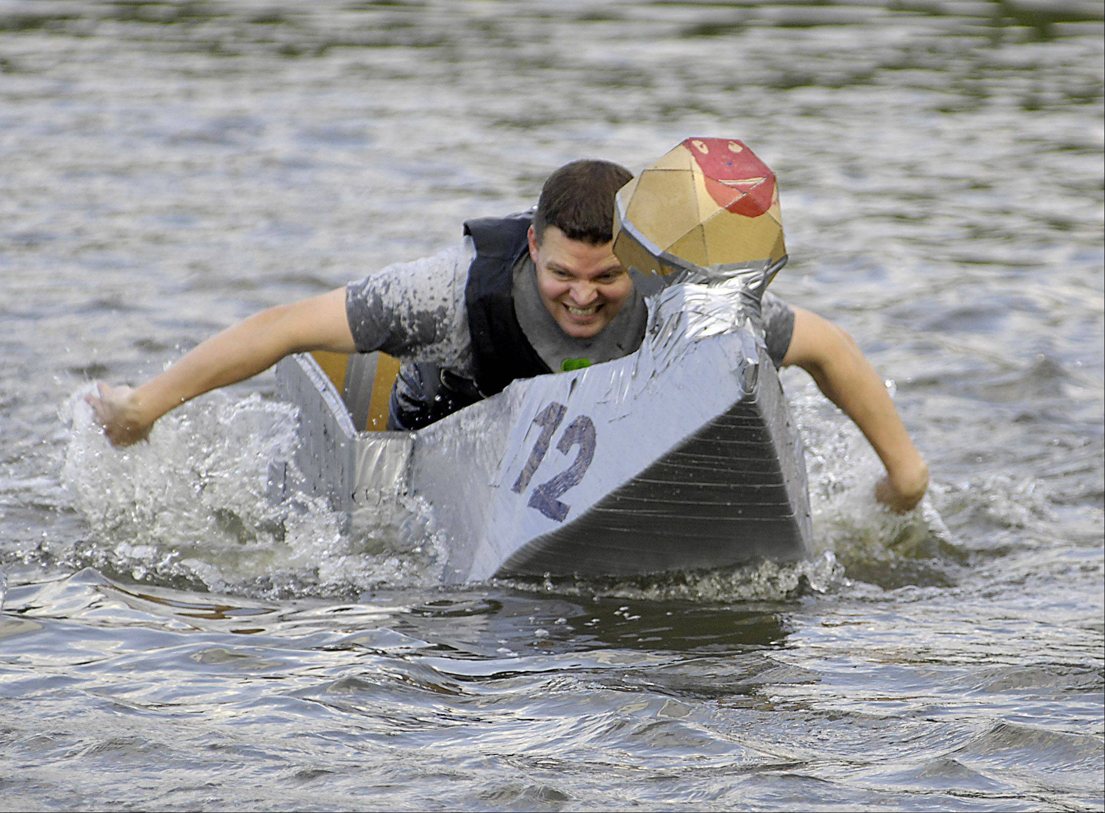 Joe Schneider, 32, of Algonquin, powers his cardboard boat through the choppy waters of the Fox River for a third-place finish at the annual cardboard boat regatta at a previous Algonquin Founders' Days festival. All 110 competitors were given their supplies and had less than two hours to design and build their boat on the shore of the Fox River.