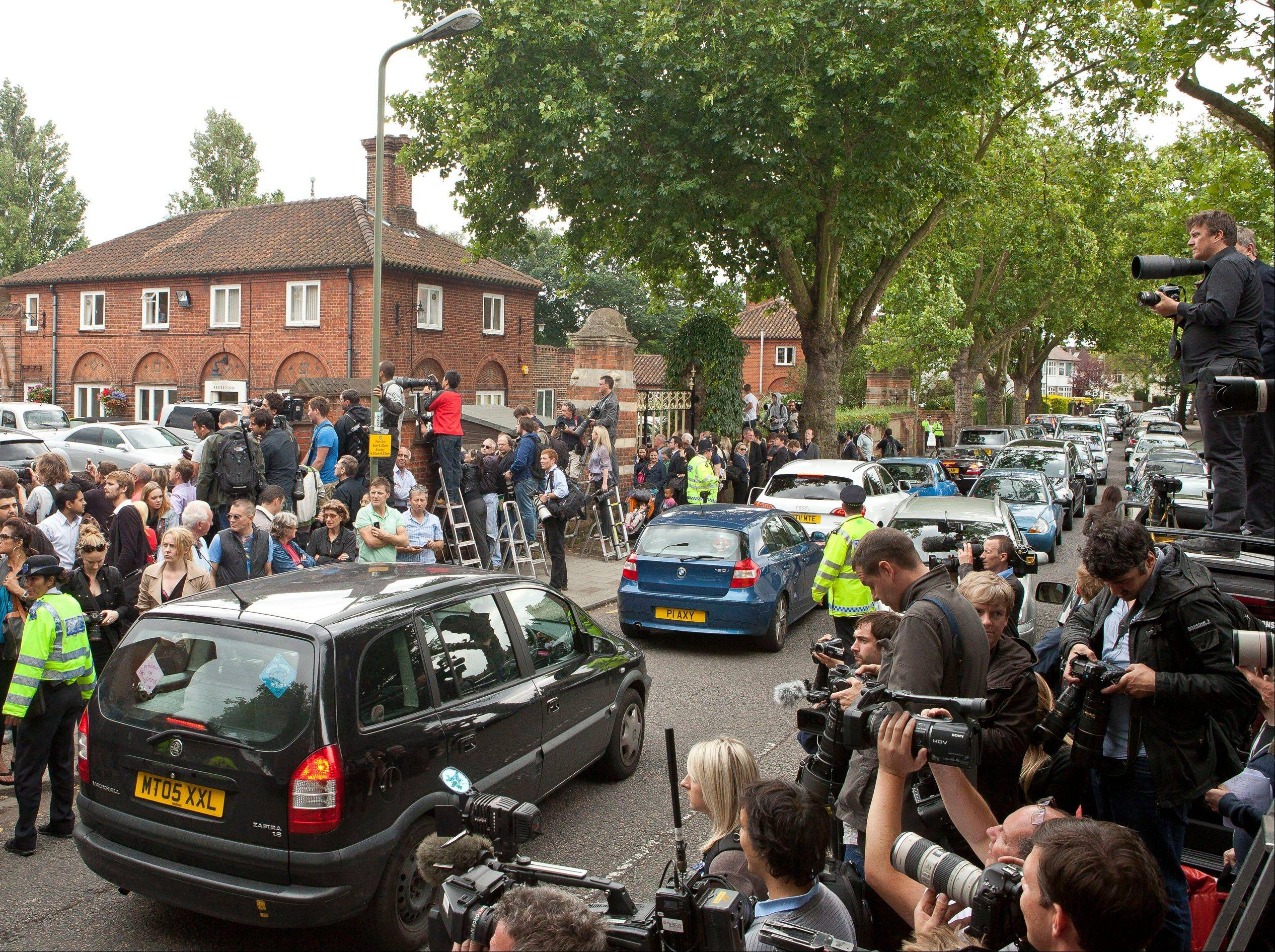 Members of the media gather outside the entrance to Golders Green Crematorium in London, Tuesday July 26, 2011, as mourners arrive for the funeral of singer Amy Winehouse. The soul diva, who had battled alcohol and drug addiction, was found dead Saturday at her London home. She was 27.