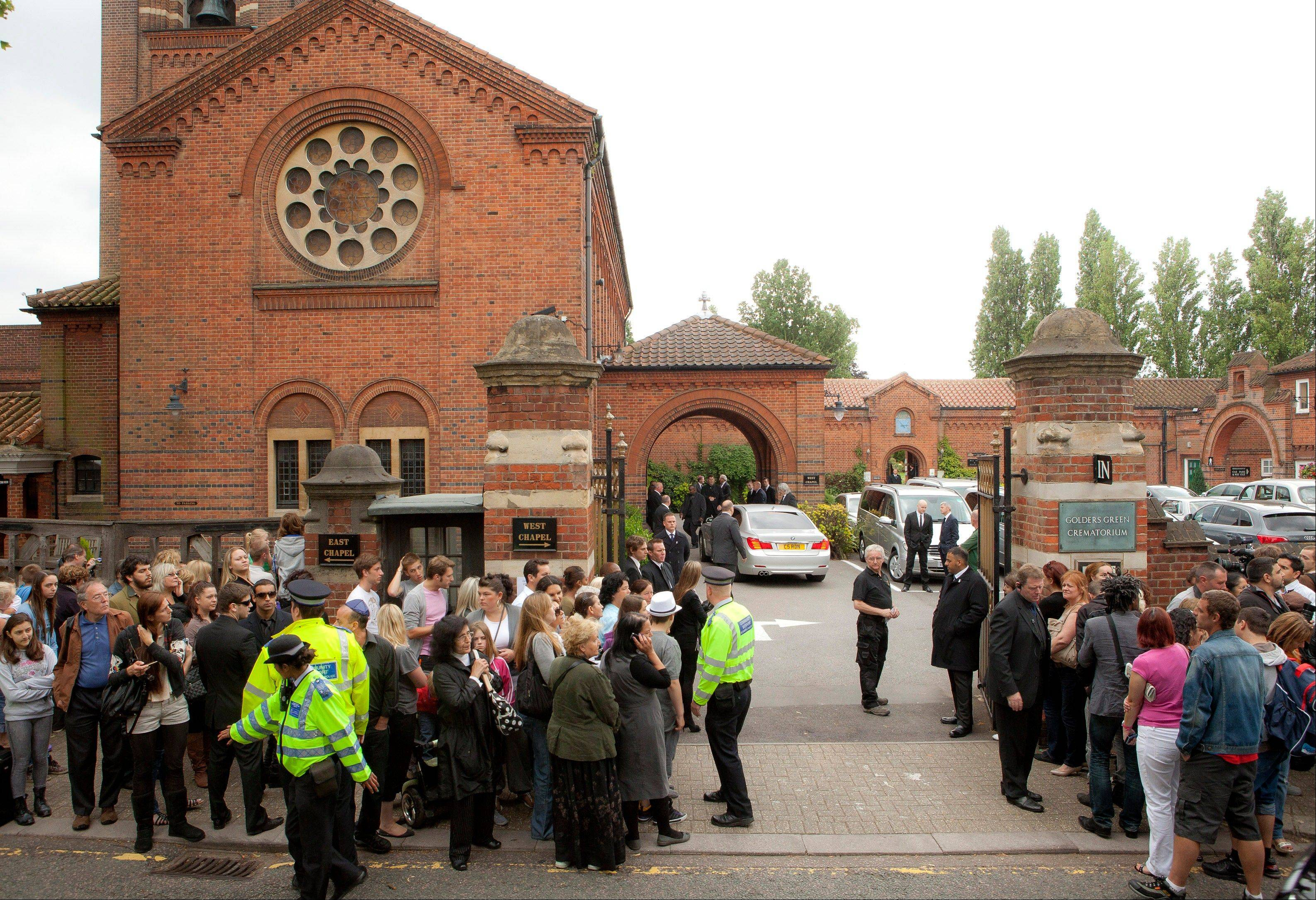 Members of the public gather opposite Golders Green Crematorium for the funeral ceremony of British singer Amy Winehouse, north London, Tuesday, July 26, 2011. Winehouse, who had battled alcohol and drug addiction, was found dead Saturday at her London home. She was 27.