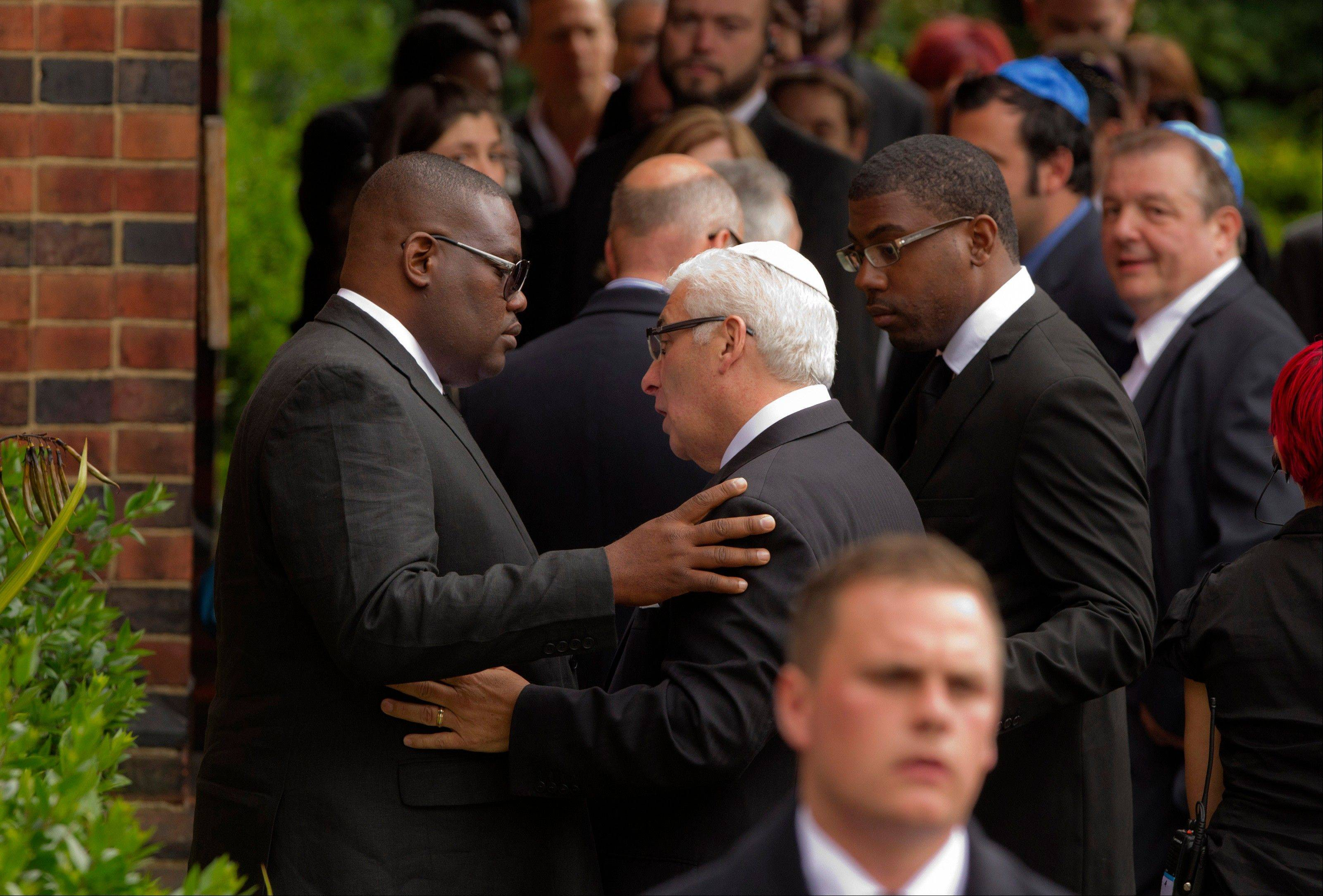 British singer Amy Winehouse's father Mitch, center, is consoled as he arrives at Golders Green Crematorium for the funeral ceremony of his daughter, north London, Tuesday, July 26, 2011.