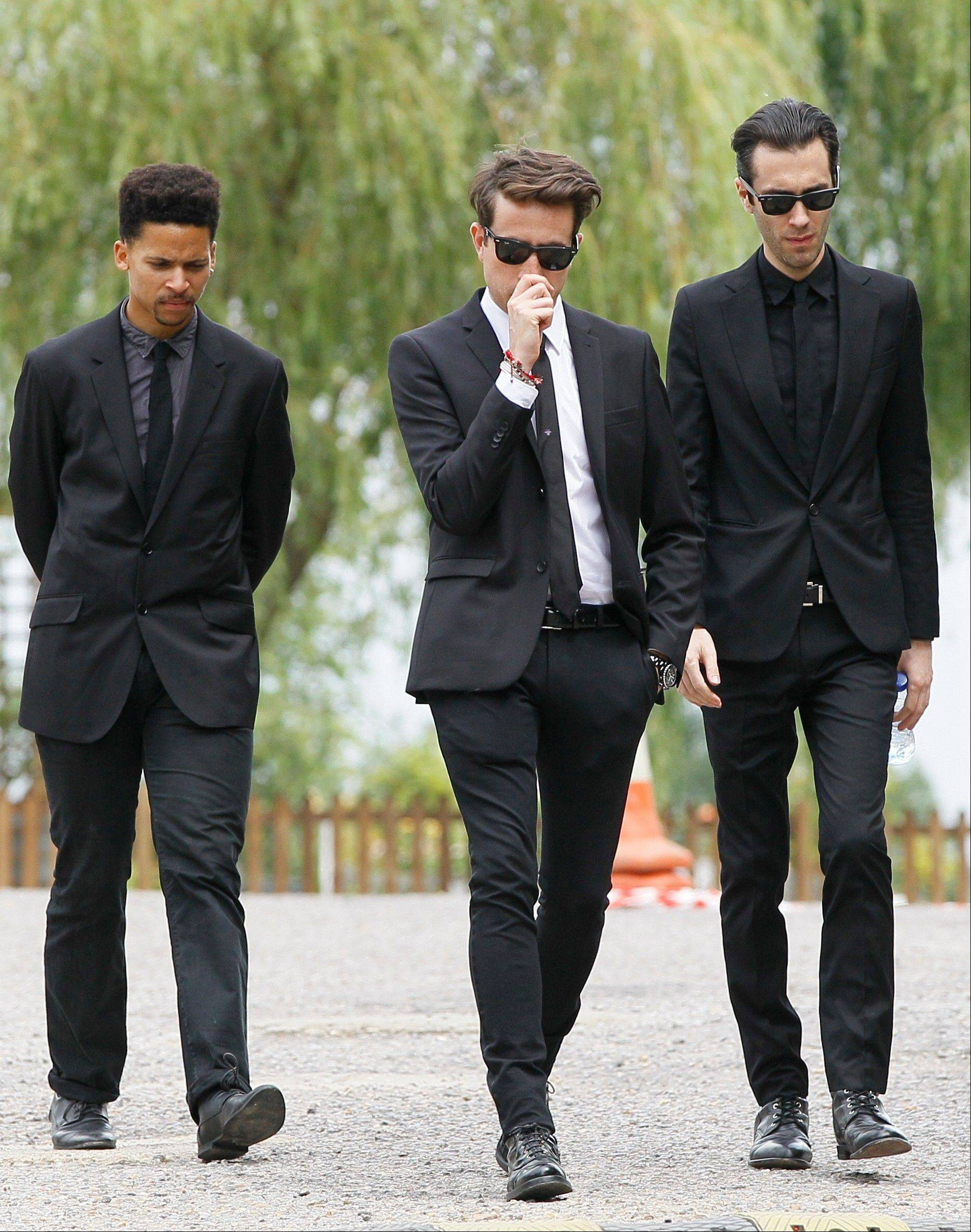 Radio dj Nick Grimshaw, centre, and two other mourners leave Edgwarebury Cemetery, in London, Tuesday July 26, 2011, after attending the funeral of singer Amy Winehouse.