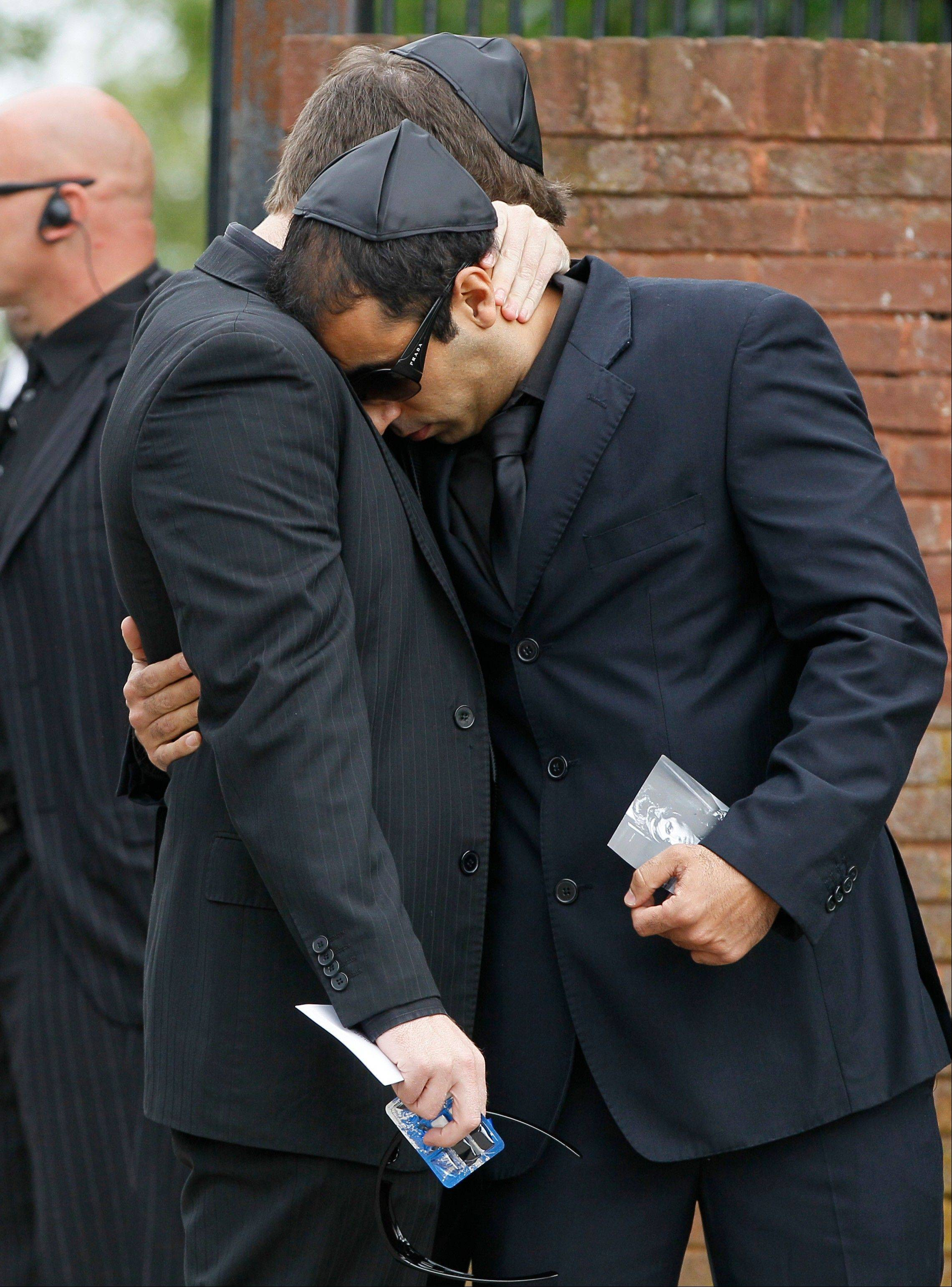 Two unidentified mourners embrace as they leave Edgwarebury Cemetery, in London, Tuesday July 26, 2011, after attending the funeral of singer Amy Winehouse.