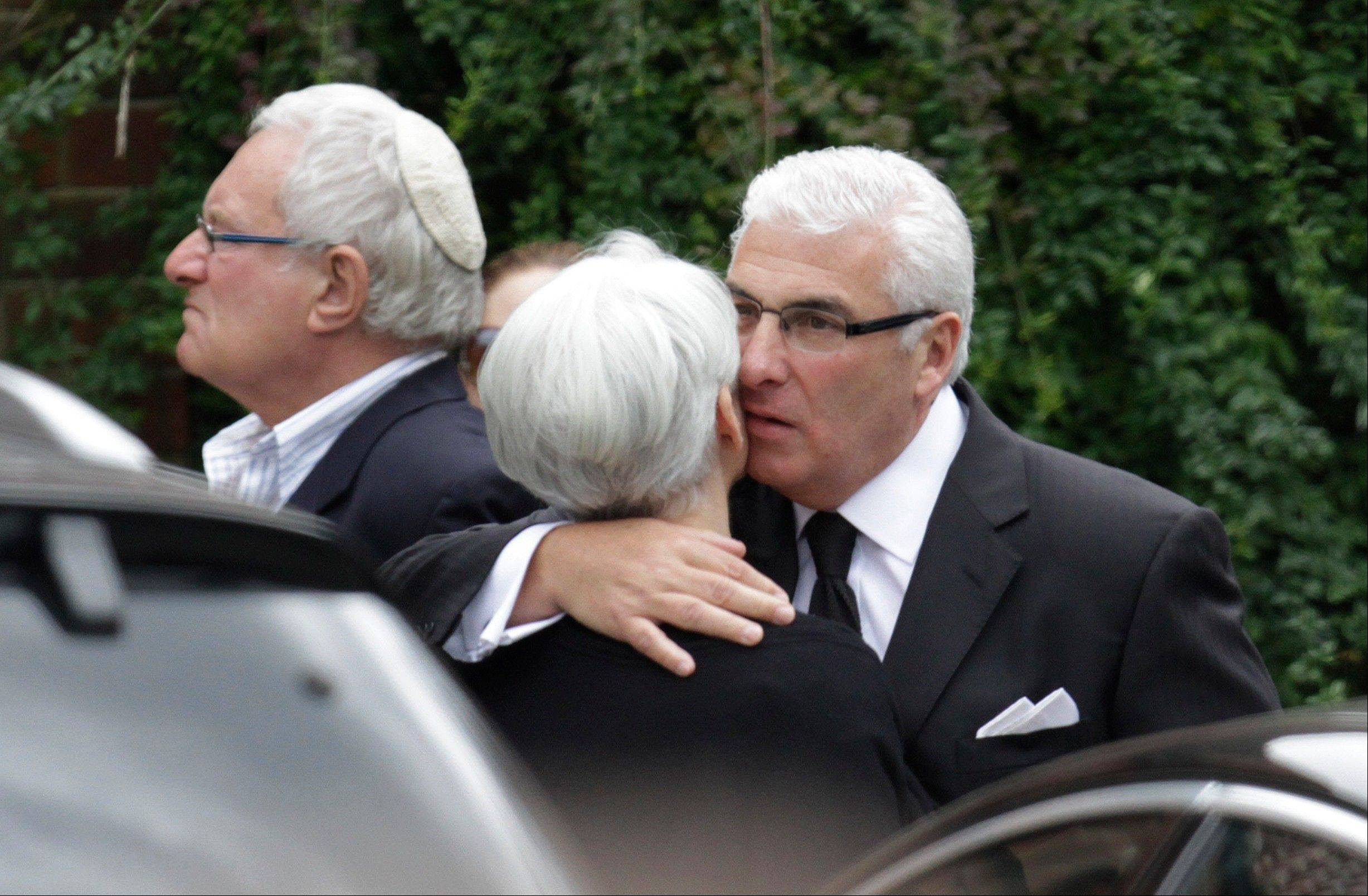 Mitch Winehouse, right, the father of British singer Amy Winehouse, consoles a mourner as he leaves the Golders Green Crematorium, north London, Tuesday, July 26, 2011. Amy Winehouse, the soul diva, who had battled alcohol and drug addiction, was found dead Saturday at her London home. She was 27.