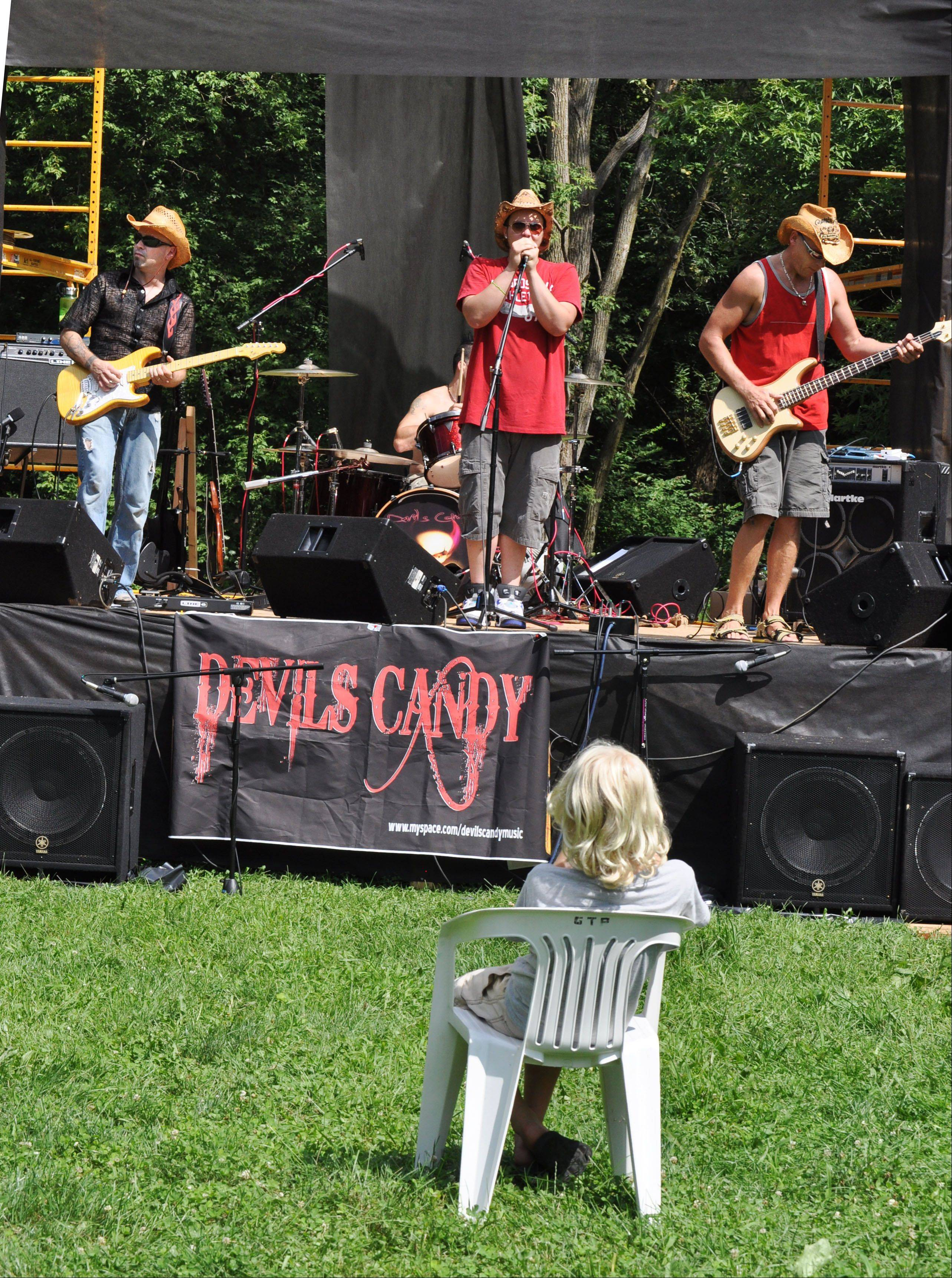 Elliot Bruno, 10, of Plainfield takes in Devil's Candy, a band playing at the Waking the Dead stage during the second annual Anonapalooza Family Summerfest in Geneva. This year's festival is set for July 30-31 and will feature 40 bands in an alcohol-free environment.
