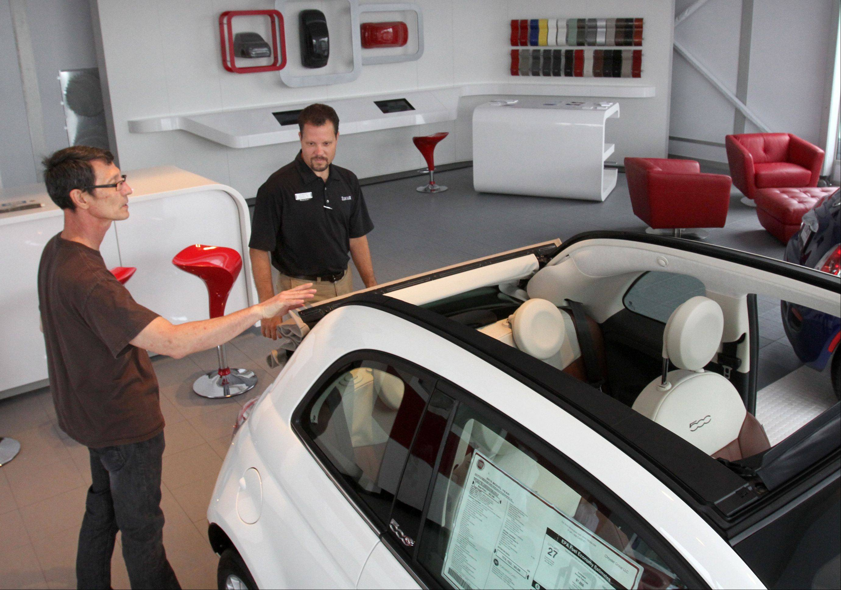 Jeff Nemcher, sales associate at Zeigler Chrysler Dodge Jeep, shows Wesley Hawk of Bartlett the 2012 Fiat 500 Lounge car in the dealership�s showroom in Schaumburg on Wednesday. The dealership was chosen to help reintroduce the Fiat brand to the U.S. market.