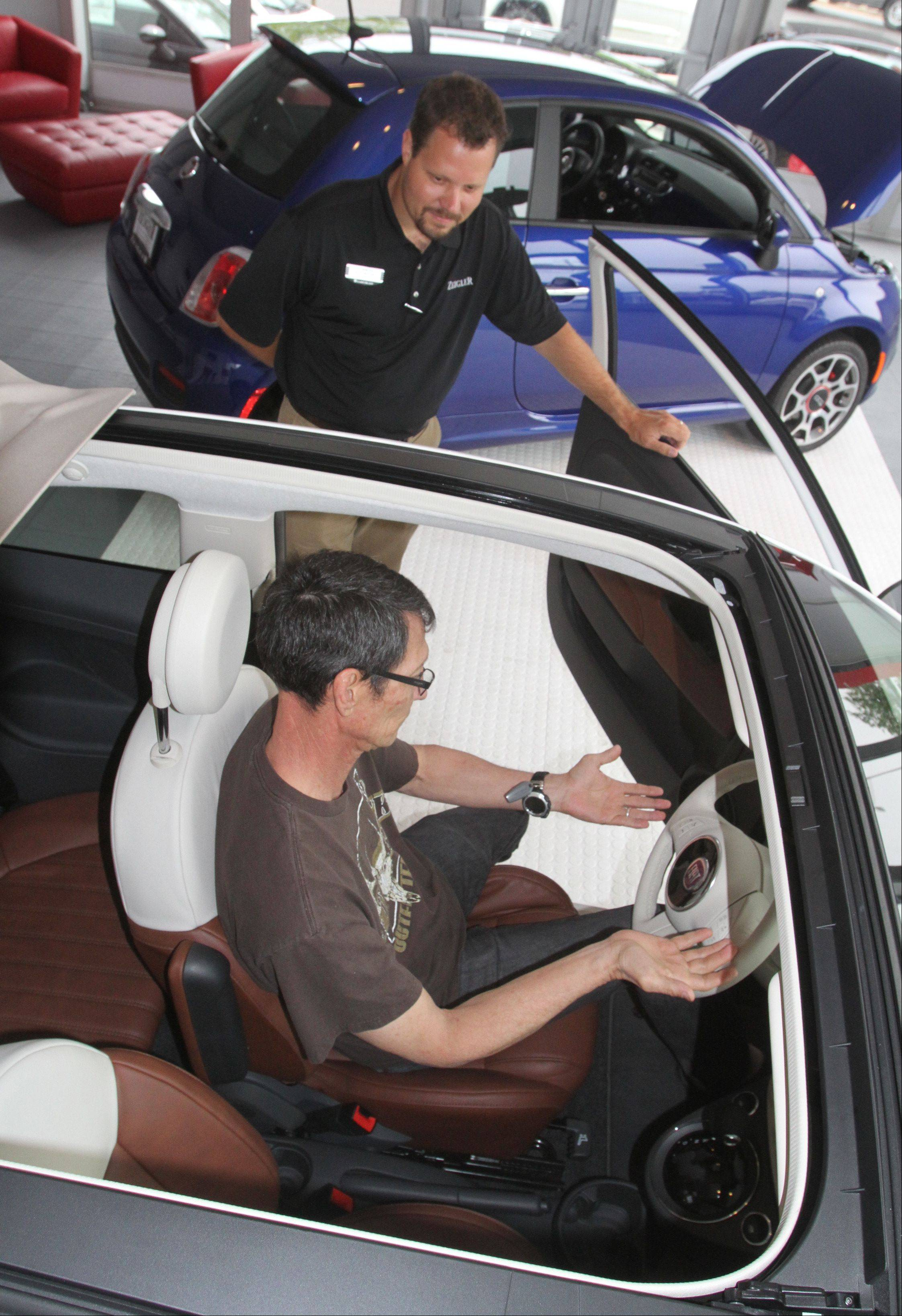 Jeff Nemcher, sales associate at Zeigler Chrysler Dodge Jeep, shows Wesley Hawk of Bartlett the 2012 Fiat 500 Pop car in the dealership's showroom in Schaumburg on Wednesday. The dealership is one of 300 in the country chosen to help reintroduce the Fiat brand to the U.S. market.