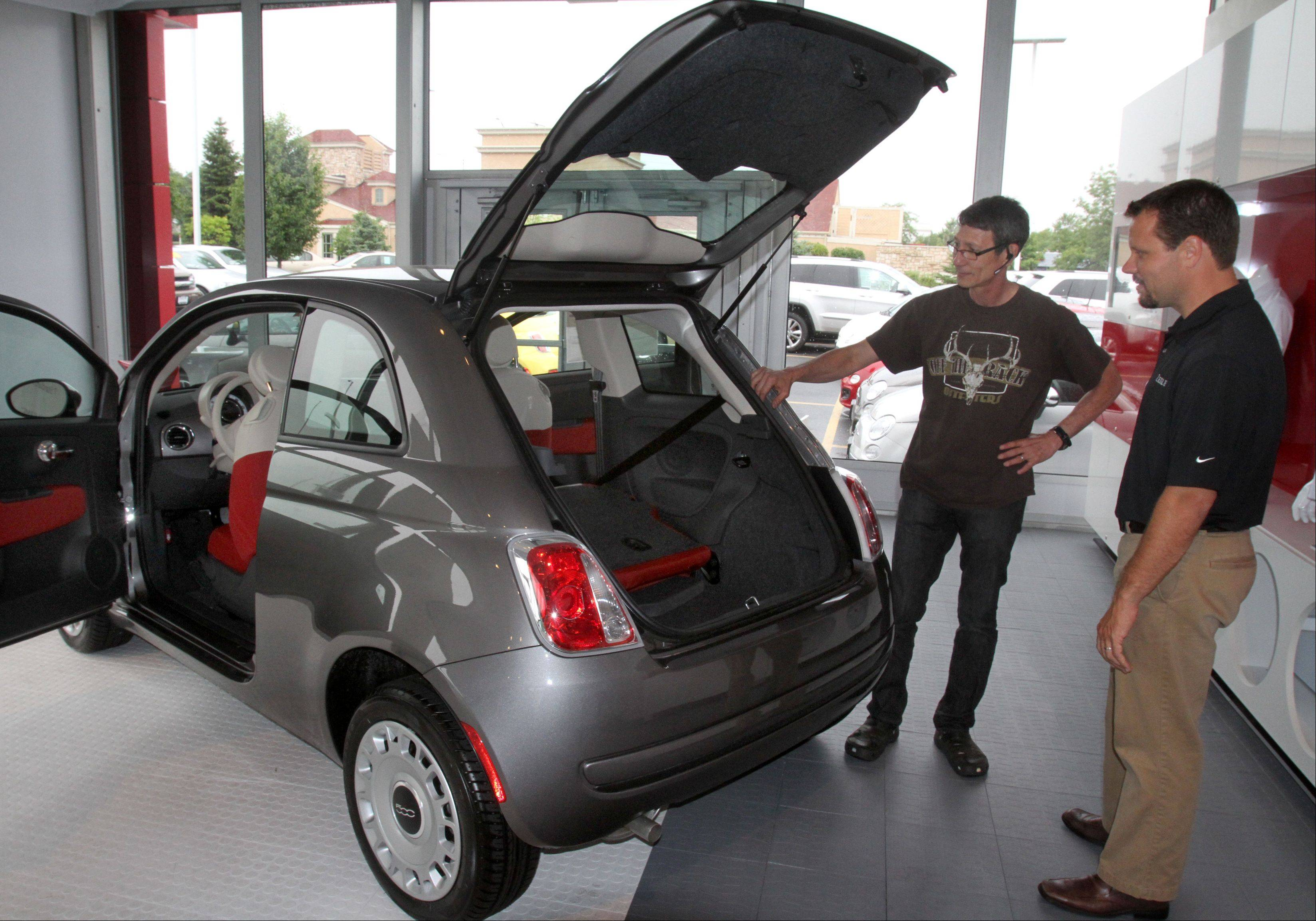 Jeff Nemcher, sales associate at Zeigler Chrysler Dodge Jeep, shows Wesley Hawk of Bartlett the 2012 Fiat 500 Pop car in the dealership's showroom in Schaumburg on Wednesday. The dealership was chosen to help reintroduce the Fiat brand to the U.S. market.