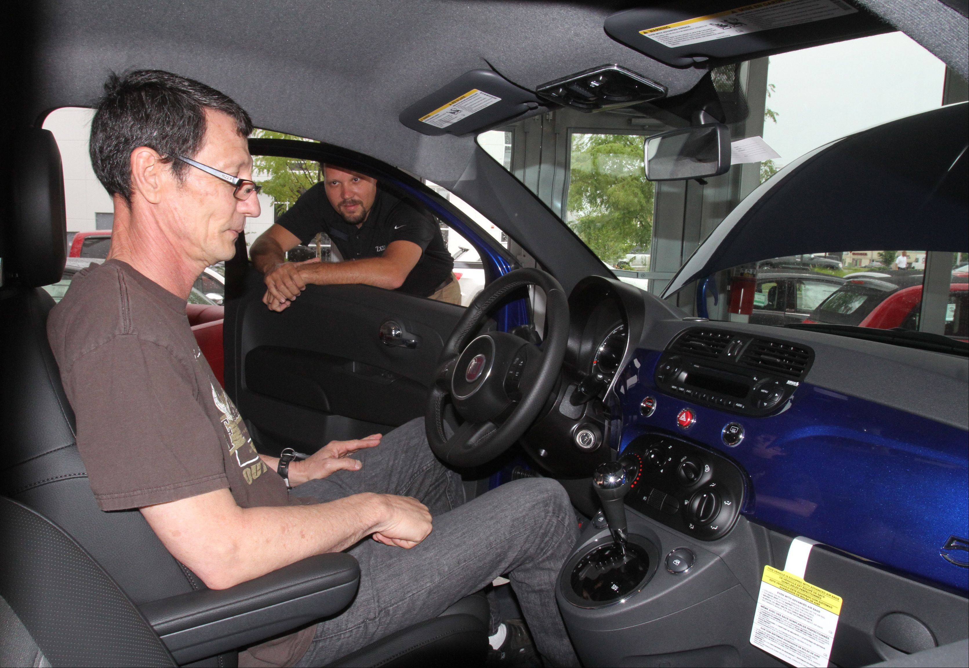 Jeff Nemcher, sales associate at Zeigler Chrysler Dodge Jeep, shows Wesley Hawk of Bartlett the 2012 Fiat 500 Sport car in the dealership's showroom in Schaumburg on Wednesday. The dealership was chosen to help reintroduce the Fiat brand to the U.S. market.