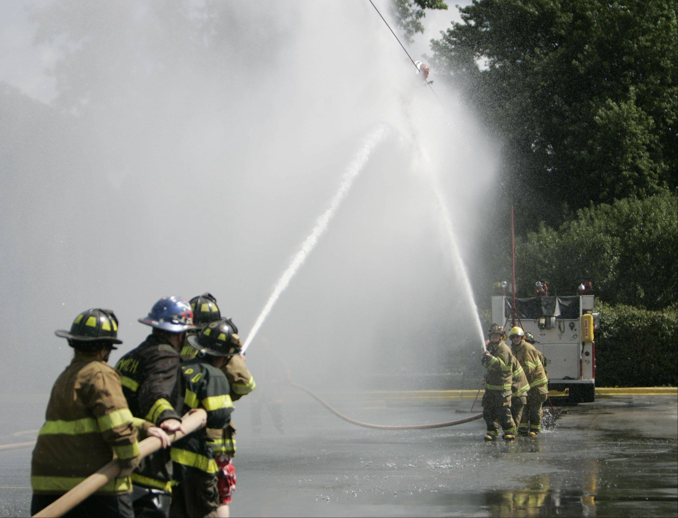 Firefighters from Sandwich, right, and Paw-Paw, left, compete in the Fire Fighters Association water fights during Sugar Grove's Corn Boil festival.