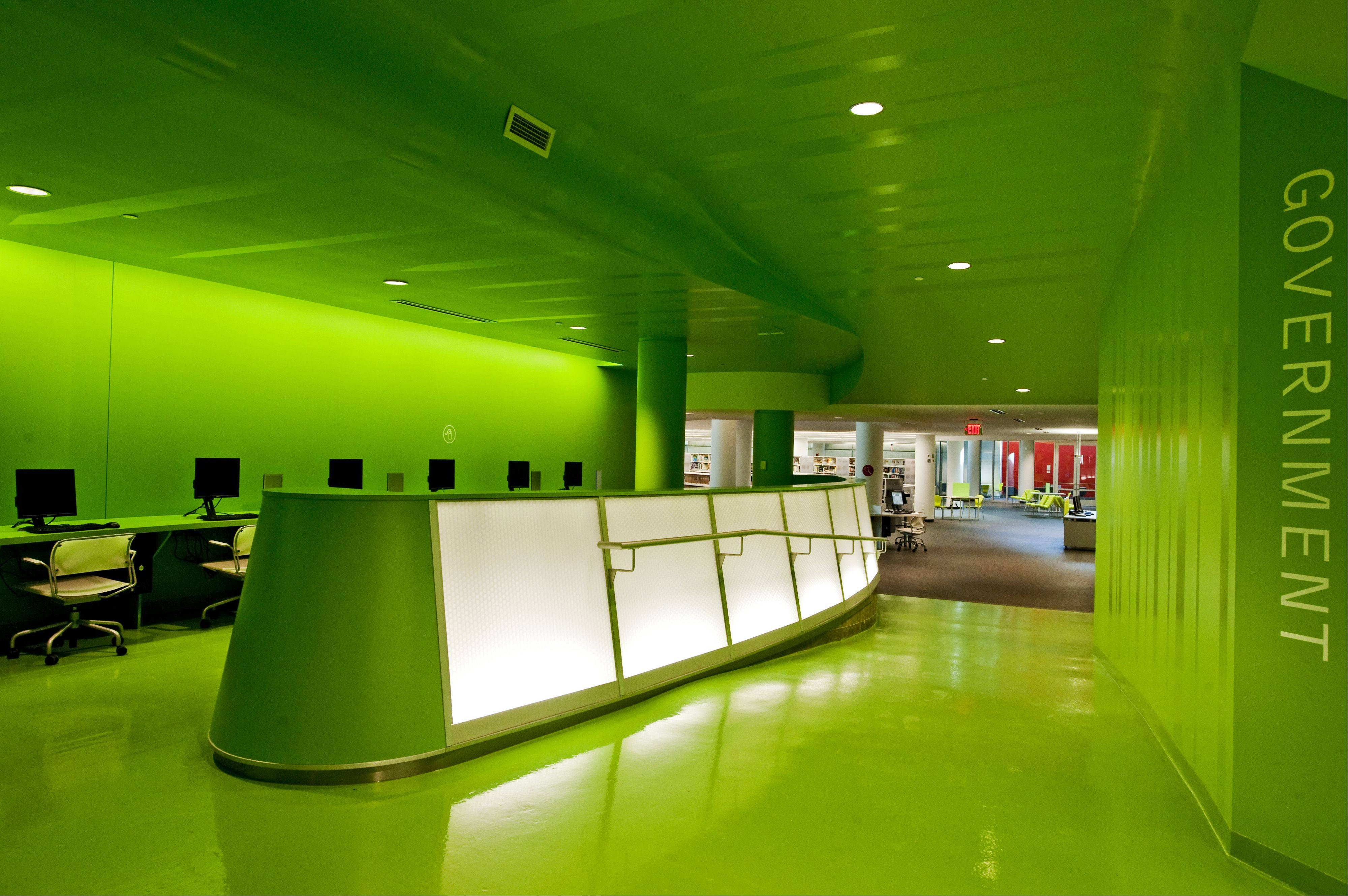 The information commons is painted in bright green and lined with computers.