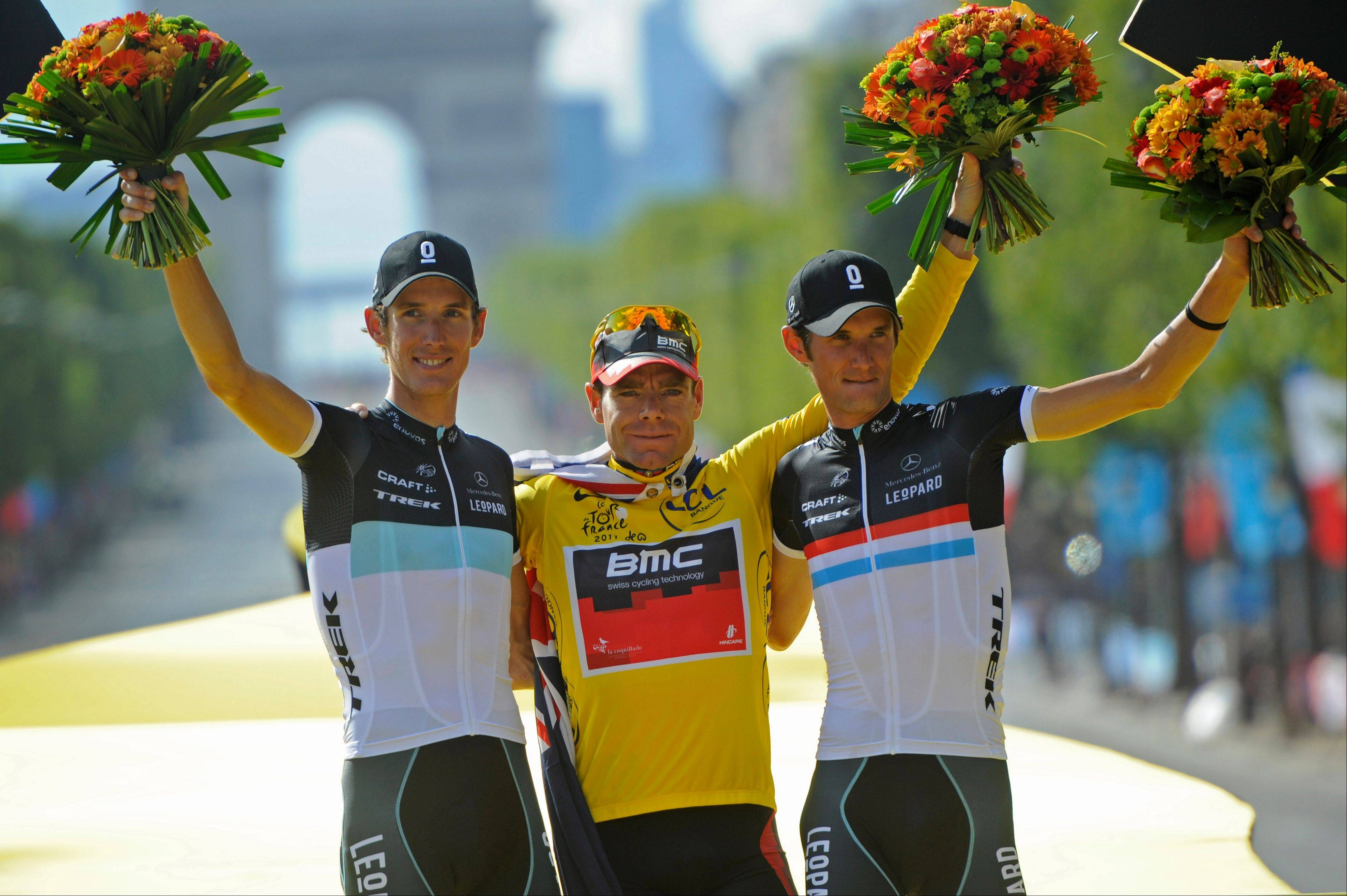 Champion Cadel Evans, middle, is flanked by second-place Andy Schleck, left, and his older brother Frank on the award podium Sunday in Paris.