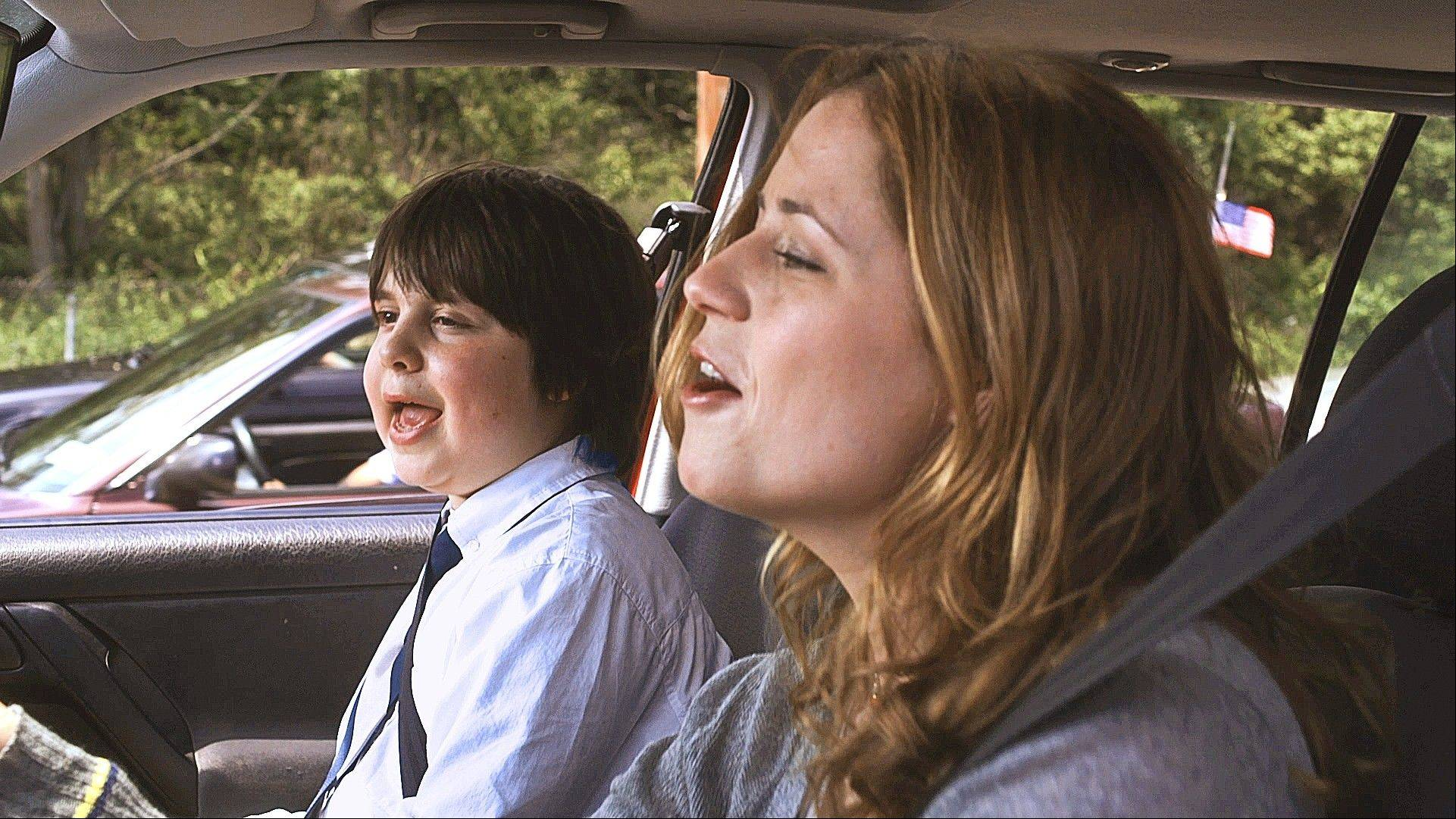 "Dennis (Daniel Yelskhy) and Laura (Jenna Fischer) participate in the radio singalong cliche in the comic domestic drama ""A Little Help."""