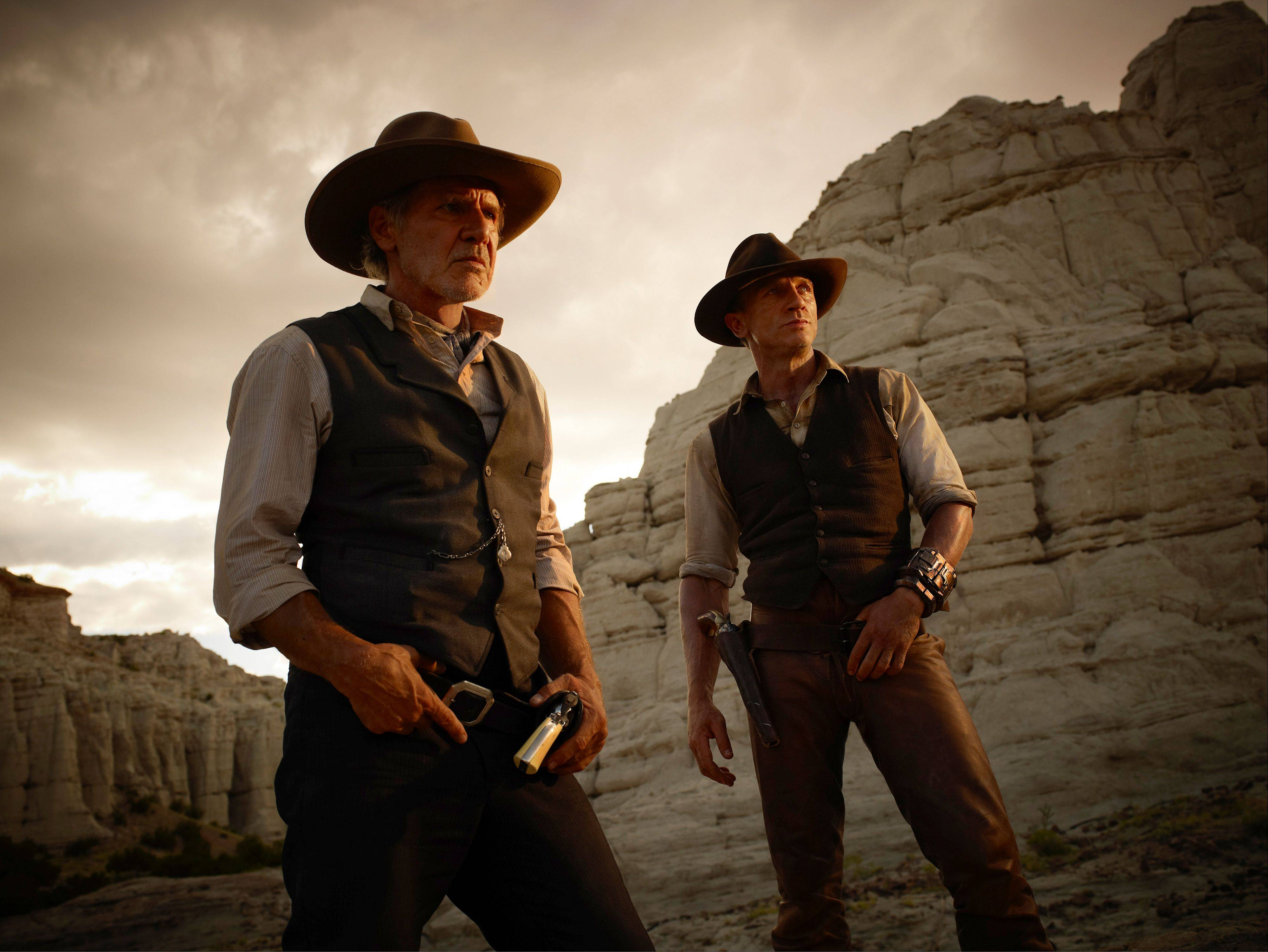 "Colonel Dolarhyde (Harrison Ford), left, and Jake Lonergan (Daniel Craig) take on some critters from outer space in the genre-busting action film ""Cowboys & Aliens."""