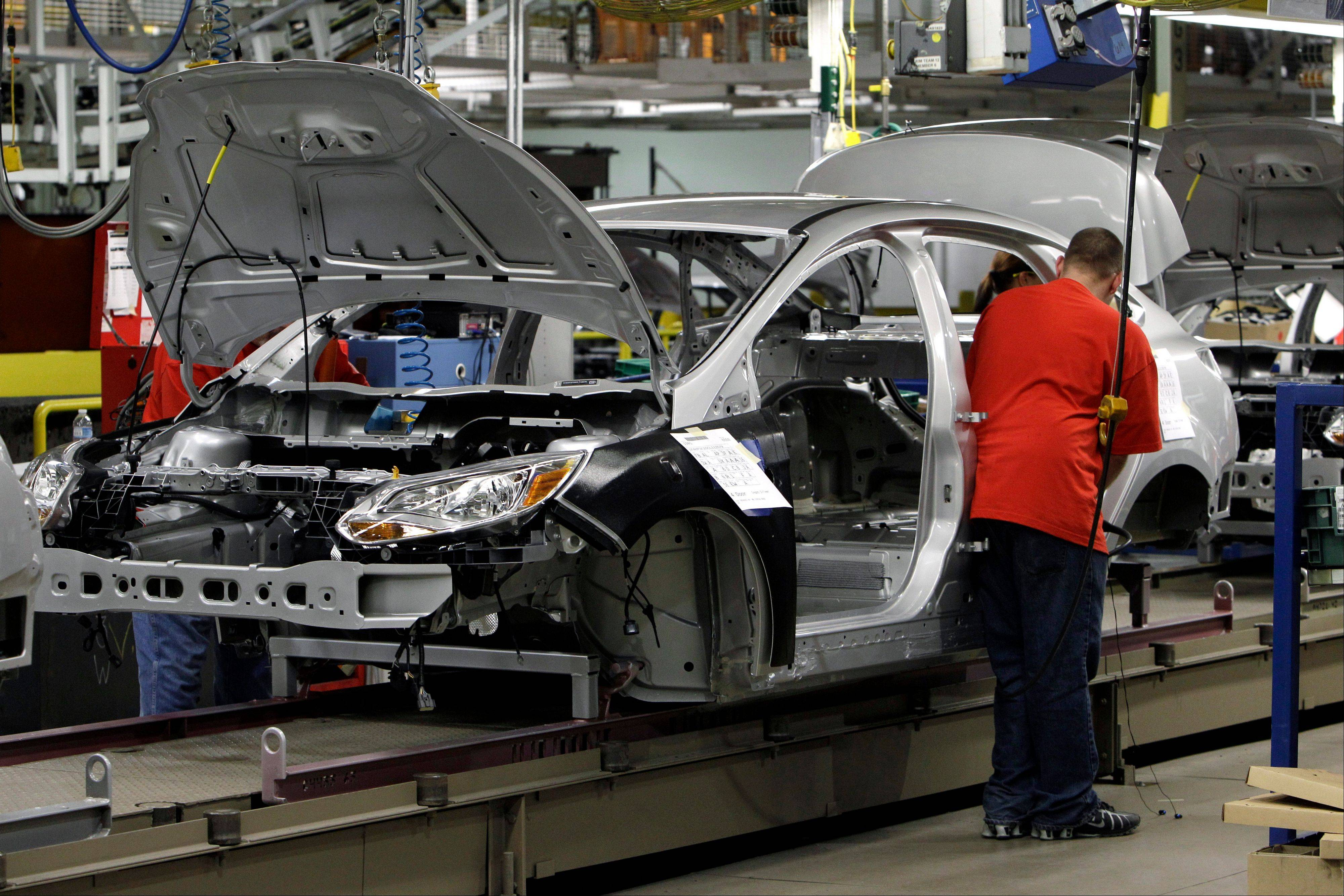 A line worker assembles a 2012 Ford Focus at the Michigan Assembly Plant in Wayne, Mich. Ford Motor Co. can�t build as many hot-selling Focus compacts as it wants to because of equipment problems at a parts factory.