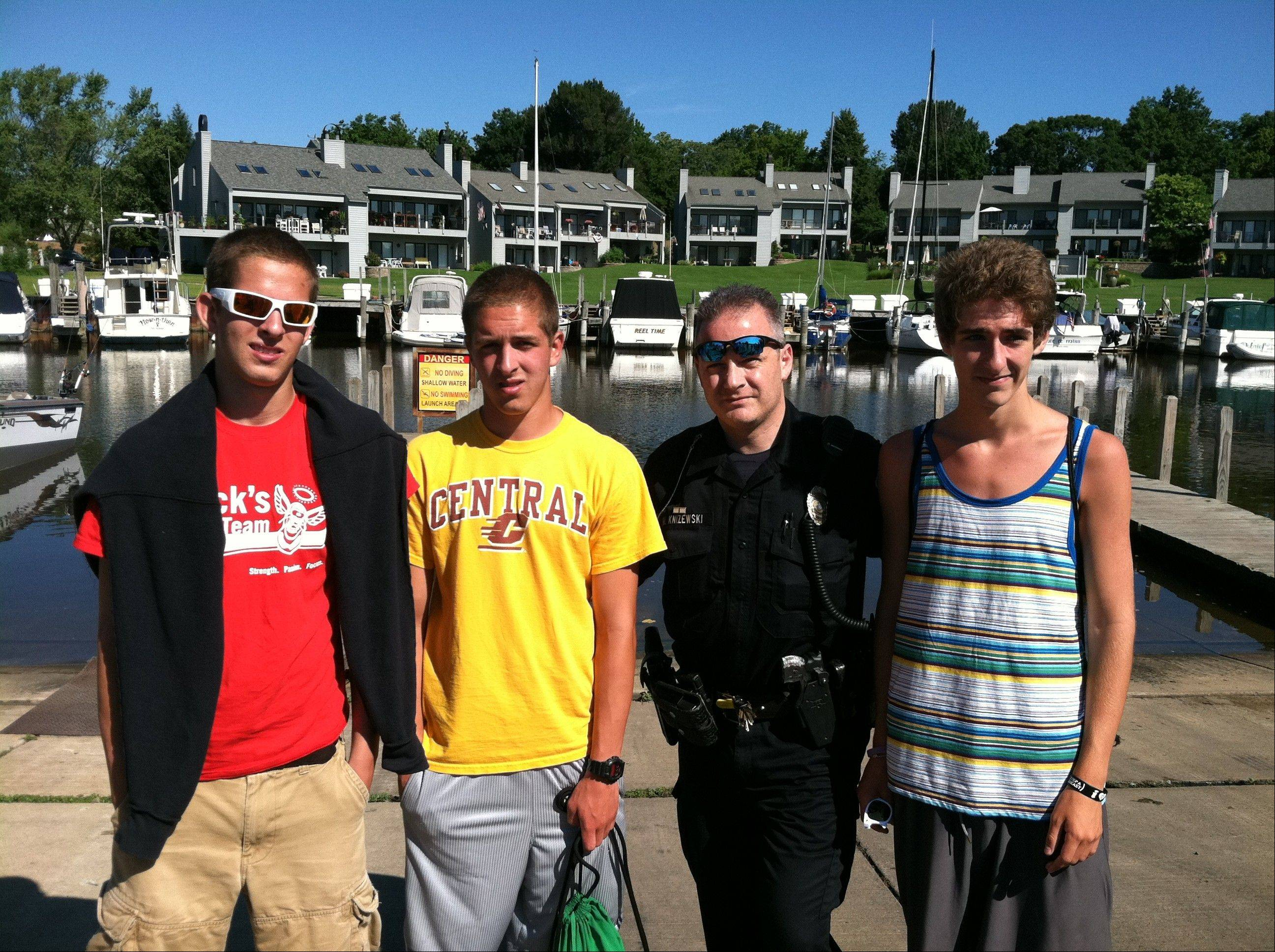From left, Glen Ellyn twins Matt and Jake Howard; South Haven, Mich. police Det. Michael Knizewski; and Davis Anderson stand on a boat dock where the three teens helped rescue and revive a man who had fallen into water on Tuesday.