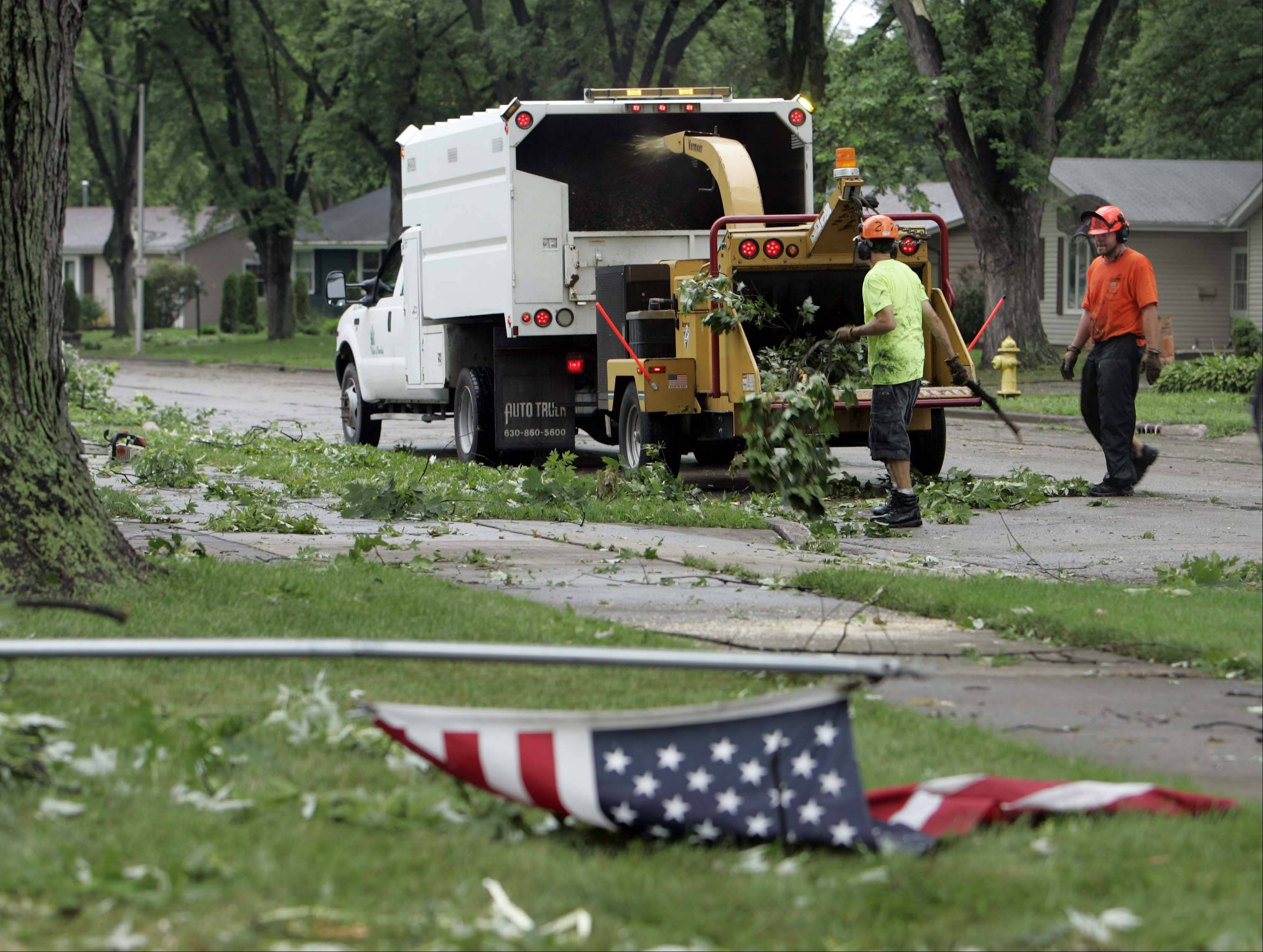 Mitch Szczepaniak, right, and Ryan Albright, from the Village of Woodridge work to clear downed trees along Thunderbird Trail in Carol Stream Thursday.