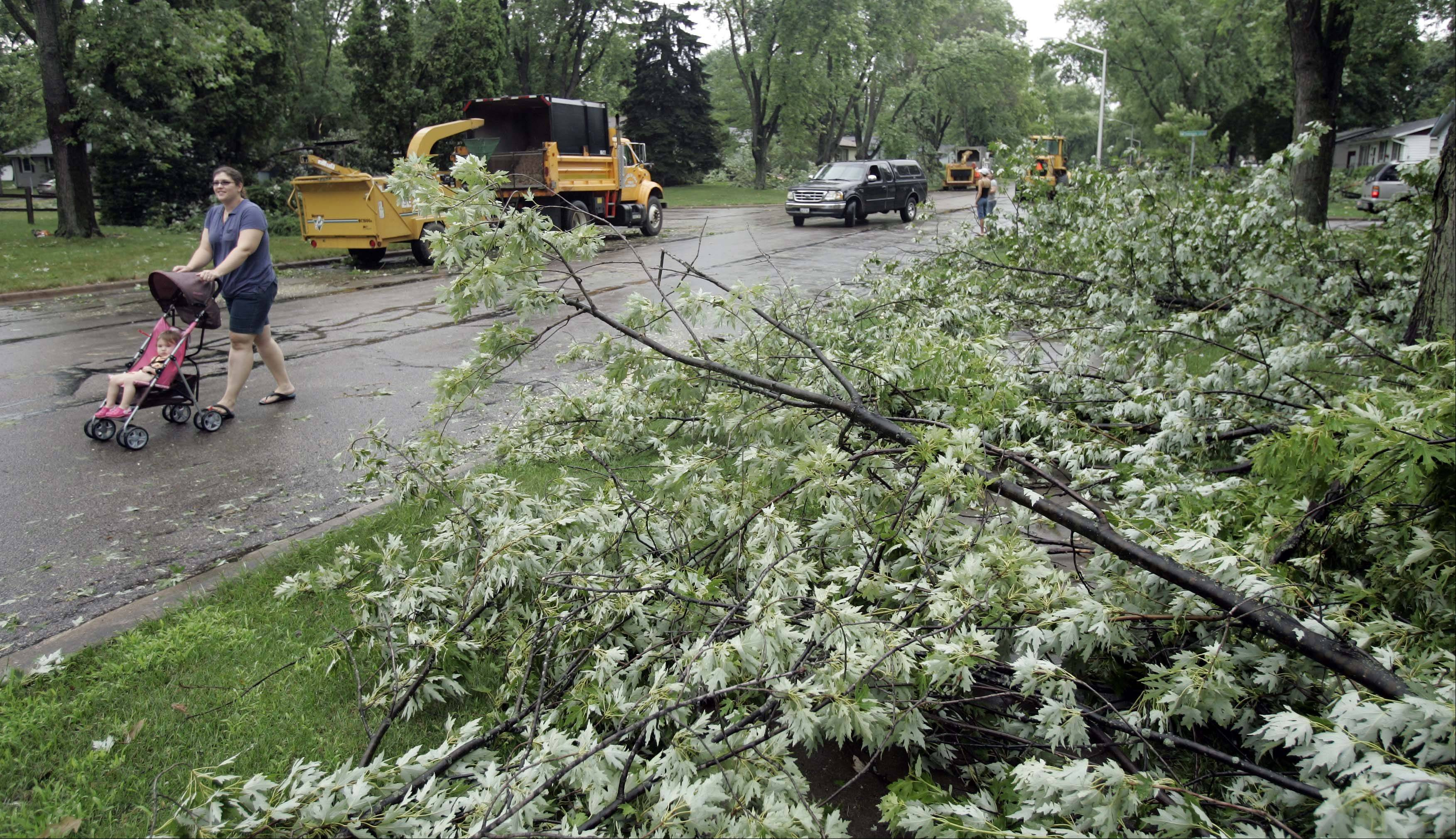 Marissa Martensen walks with her daughter Chloe, 1, past downed trees on Thunderbird Trail in Carol Stream Thursday.