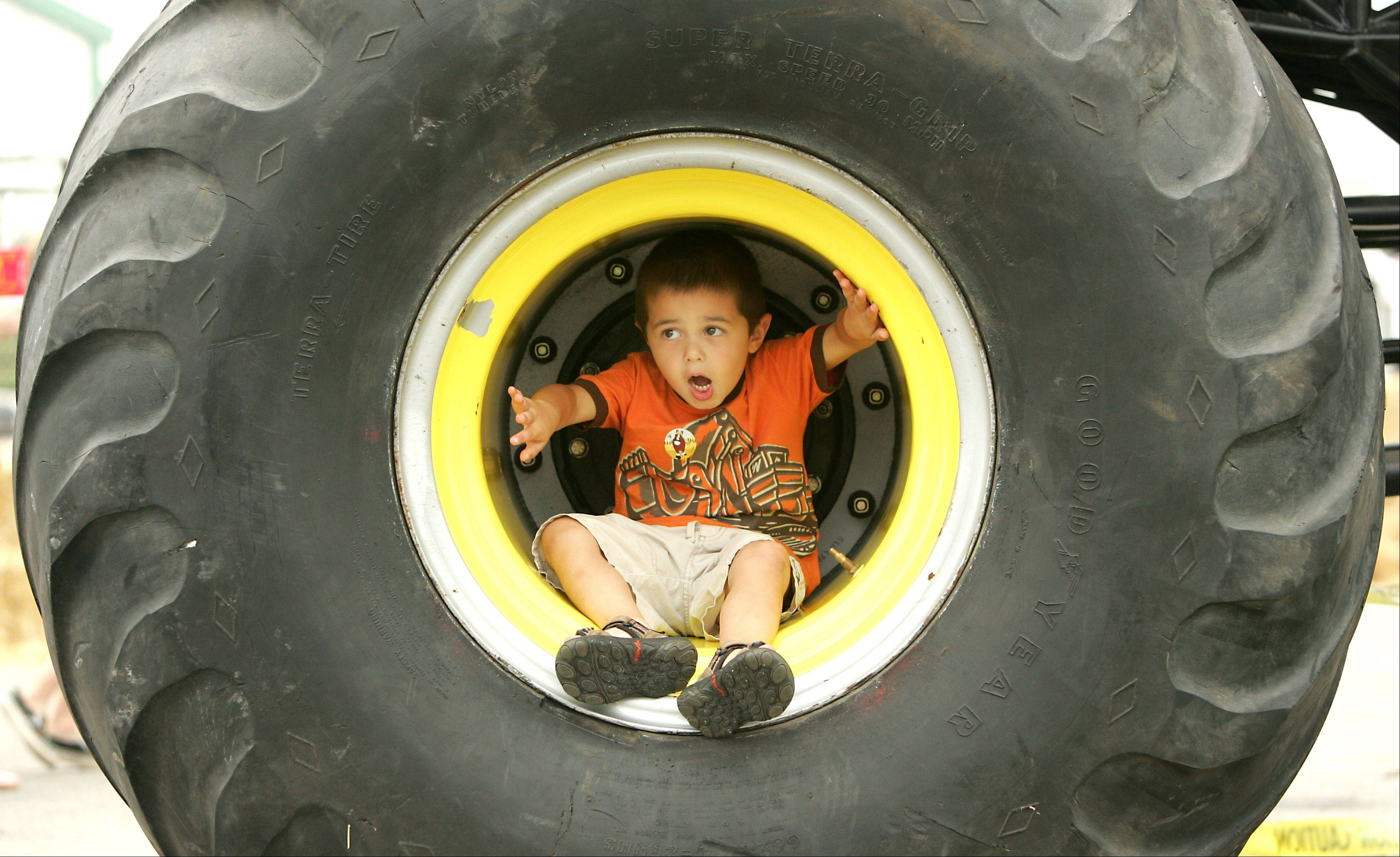 "Anthony Capasso, 4, of Chicago relaxes in the wheel of ""Outback Thunda,"" an Australian monster truck making its second U.S. appearance at the DuPage County Fair. For the first time the fair will feature a Monster Truck Thrill Show at 2 and 7 p.m. on Saturday."