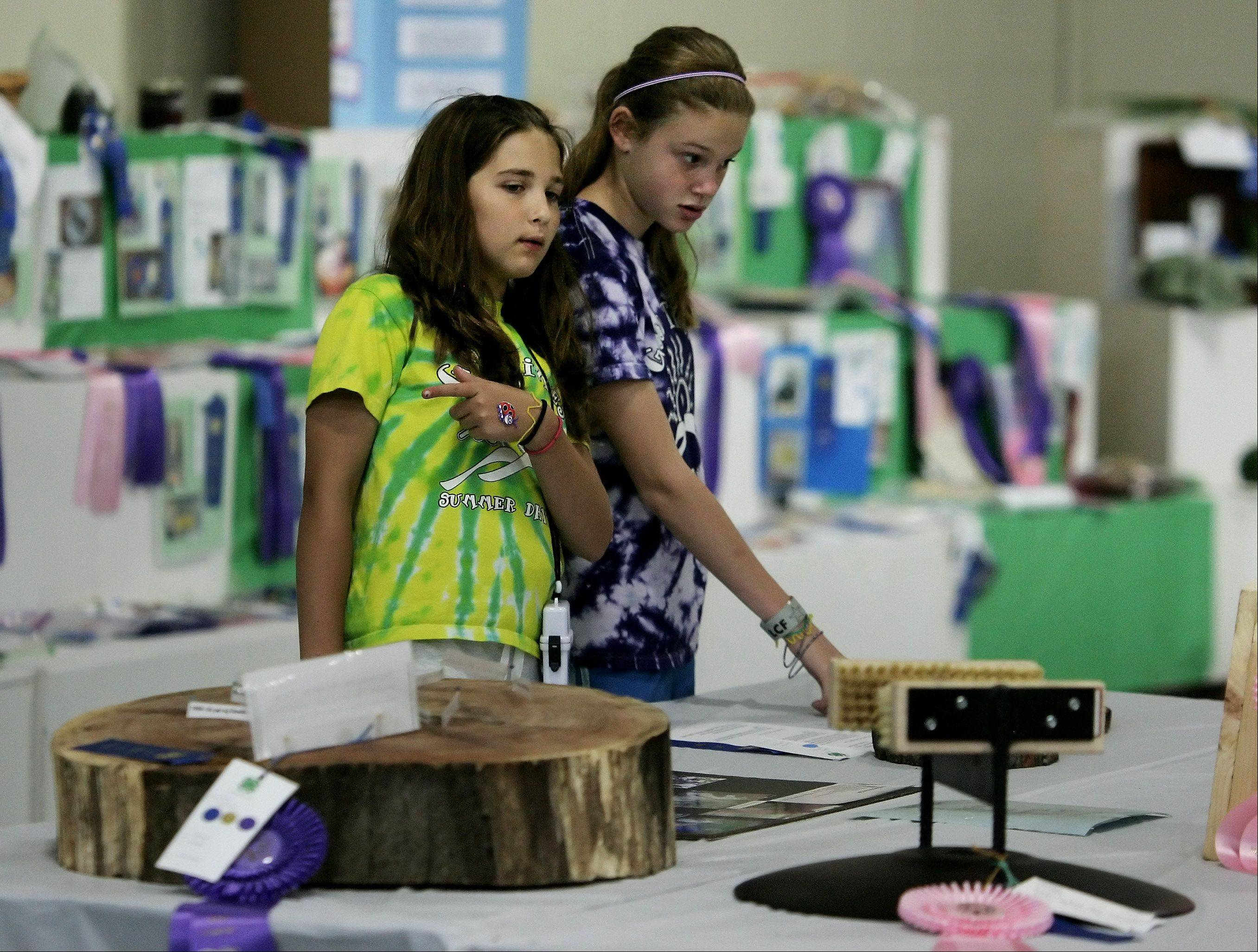 Gabby Garnowski, 11, of Arlington Heights, left, and Paige Gorman, 12, of Glenview look at 4-H club exhibits during the second day of the 83rd Annual Lake County Fair Wednesday at the fairgrounds in Grayslake.