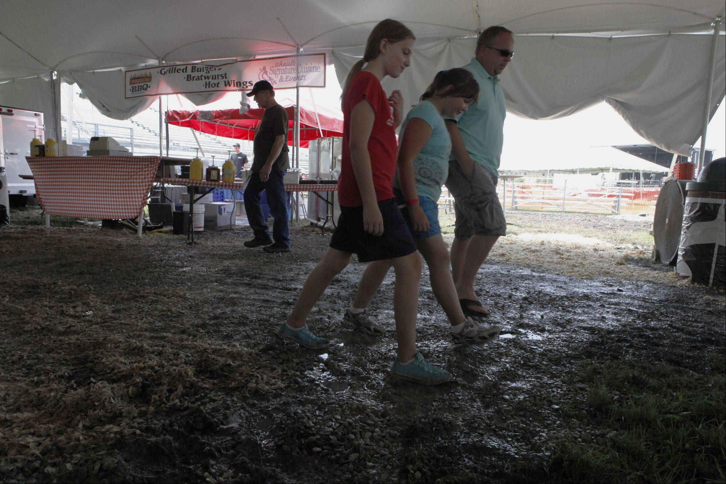The ground was muddy and wet on Friday inside the first beer and wine tent at the DuPage County Fair. Organizers believe that inclement weather is one of the reasons for a lower than anticipated attendance.
