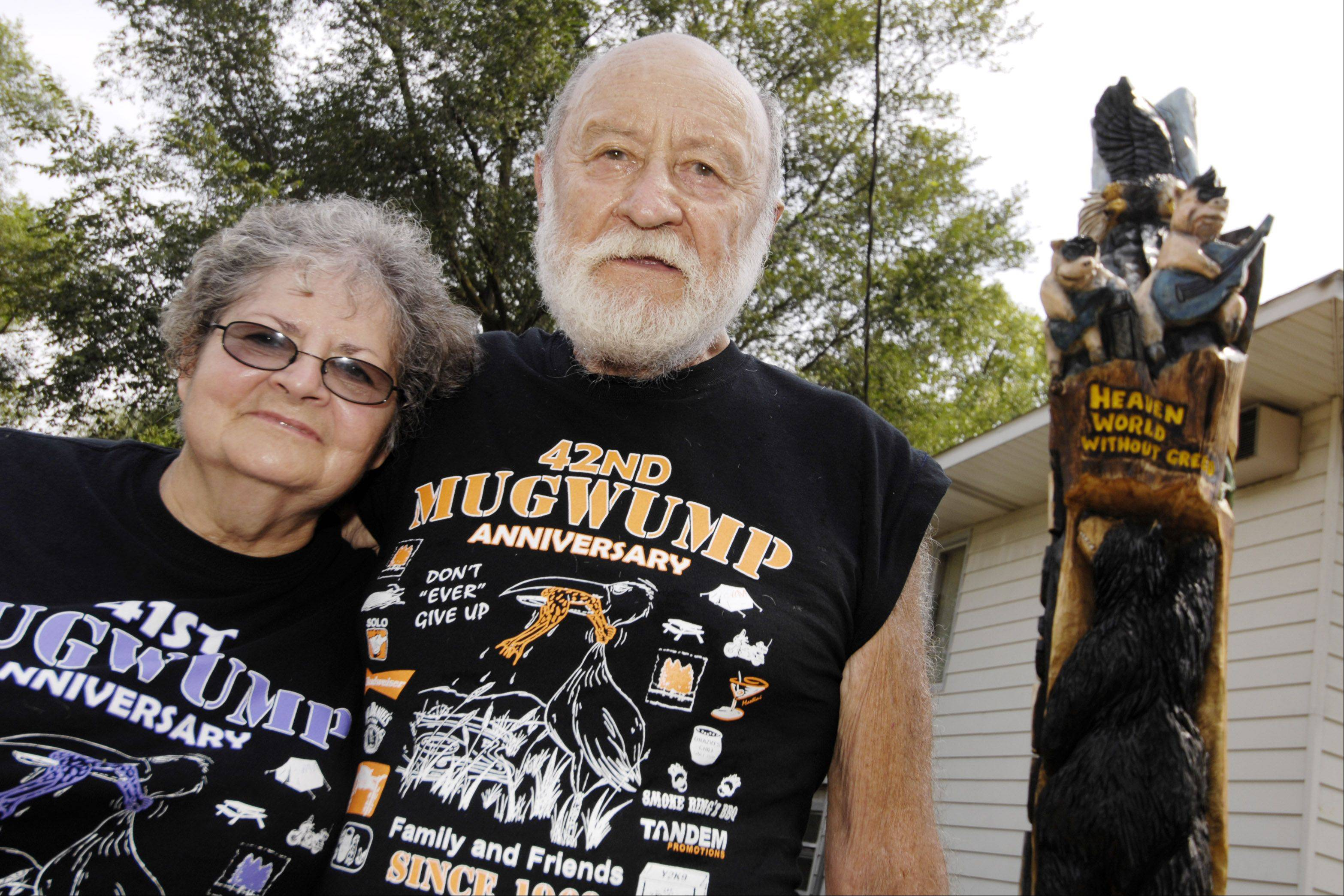 Vi and Robert Gordon stand with their new totem pole carved from a tree that was struck by lightning twice. The pole celebrates the Gordons' annual Mugwump party for family and friends, now in its 42nd year.