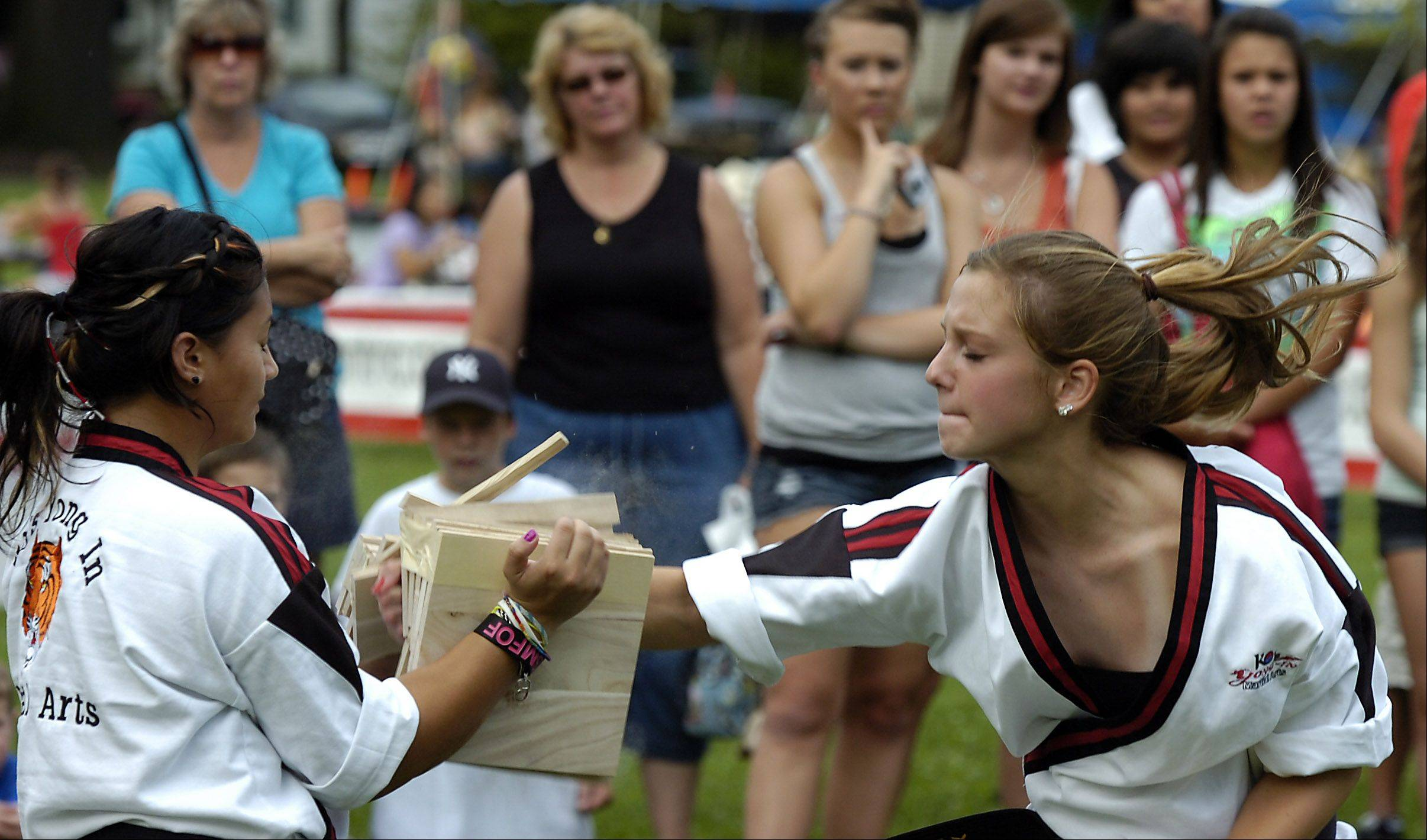 Emily Witt, 14, of Bartlett, breaks five boards held by Kate Zabat, 14, at last year�s Bartlett National Night Out in a demonstration put on by the Ko�s Yong In Team Tiger marital arts.