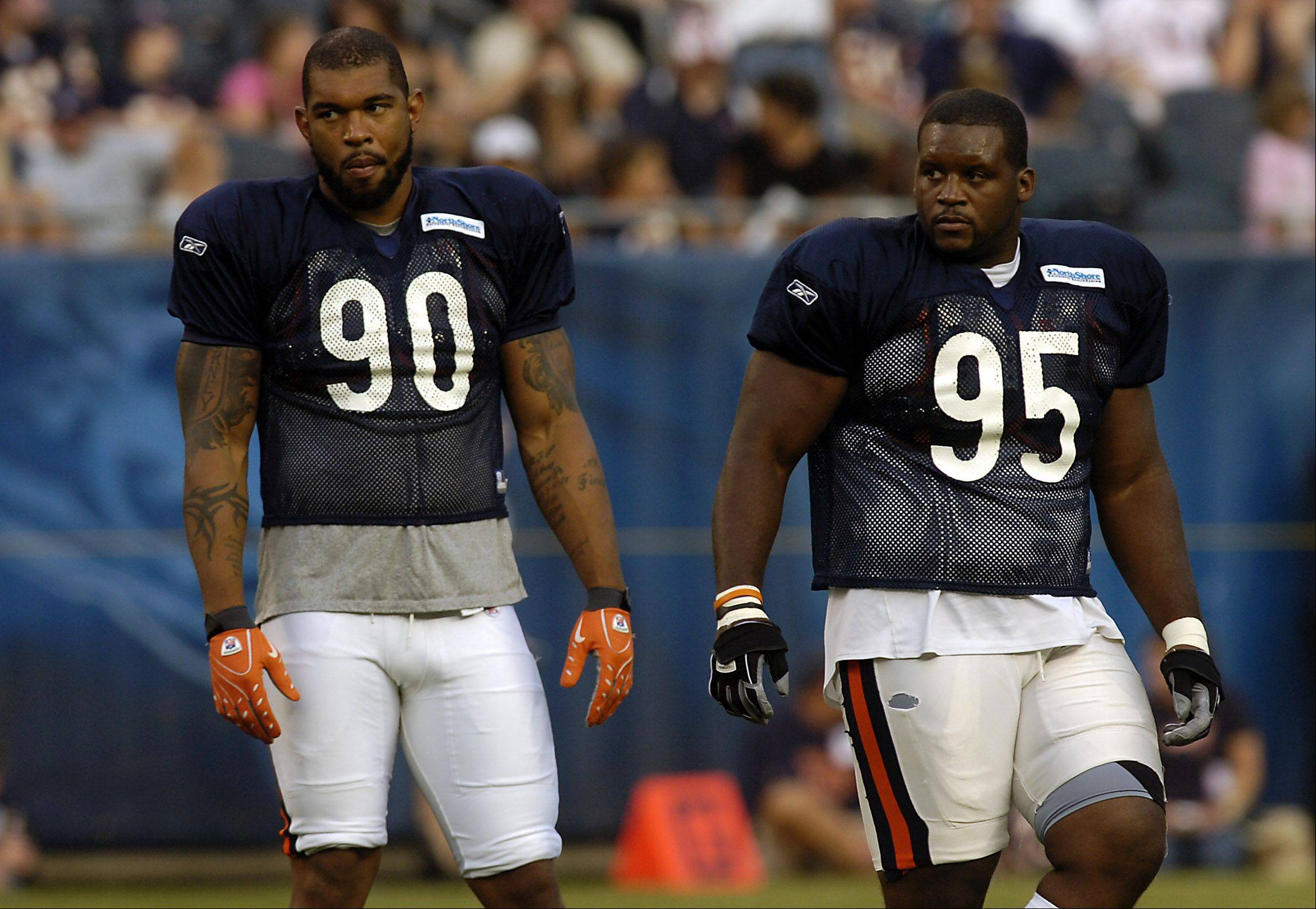 Bears defensive end Julius Peppers, left, will have tackle Anthony Adams on the defensive line again this season as Adams has signed a two-year deal to stay with the Bears.