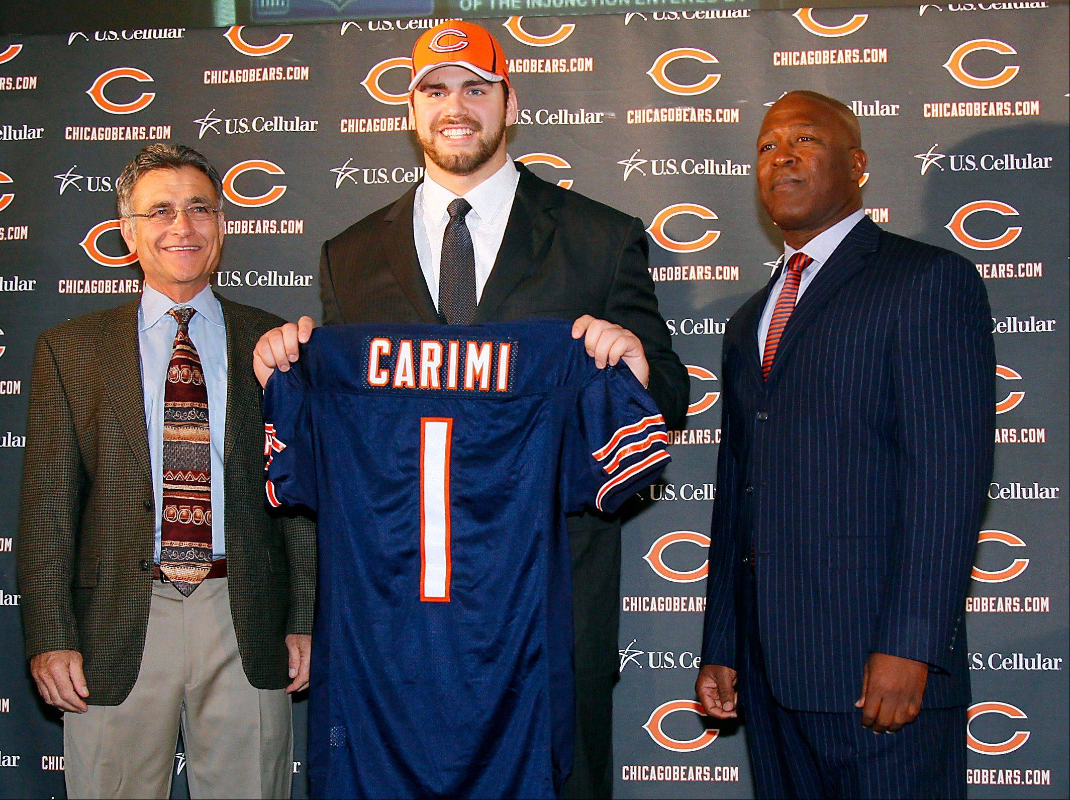 First-round draft choice Gabe Carimi, center, will join Bears general manager Jerry Angelo, left, and head coach Lovie Smith at training camp Saturday in Bourbonnais. Carimi signed a four-year deal on Friday.