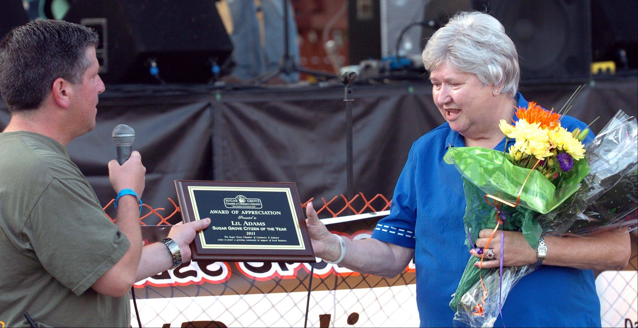 Kristin Ackmann/kackmann@dailyherald.comPresident of the Sugar Grove Chamber of Commerce and Industry, Steve Eekker, awarded Lil Adams the Sugar Grove Citizen of the Year plaque, at the Sugar Grove Corn Boil on Friday. Lil has been a resident of Sugar Grove for forty-four years, and runs the Sugar Grove Township Community House voluntarily.