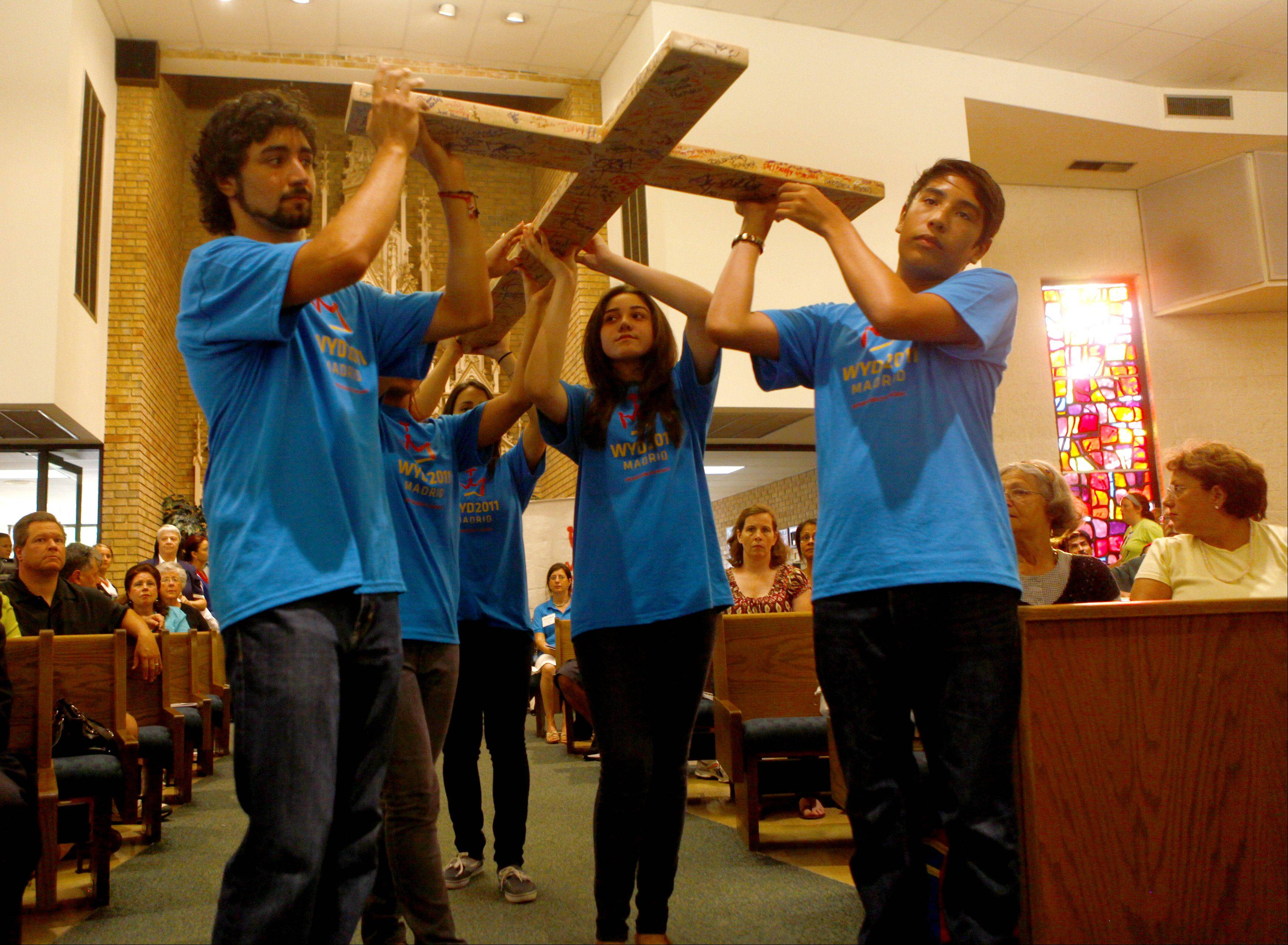 Teens participating in the World Youth Day carry a cross during Friday night Mass at St. Mary Parish in Buffalo Grove. The cross is signed by all the teens traveling to Madrid. About 500 teens from Cook and Lake county will be part of the pilgrimage in August.