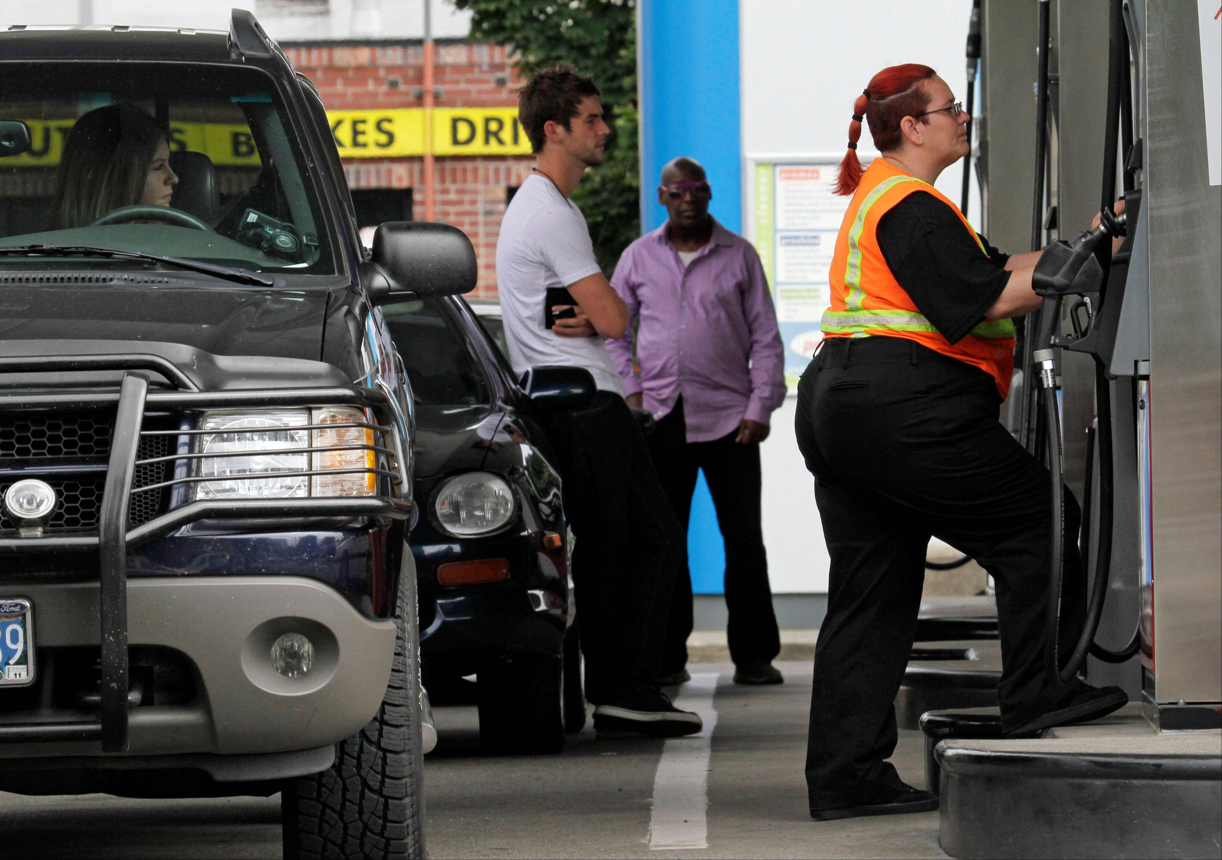 Customers stand in line as Jaqueline Henderson, right, prepares to pump gas at a station in Portland, Ore. President Barack Obama and top auto executives unveiled details of a compromise to slash the amount of gasoline cars and trucks will need down the road. The deal will double fuel economy standards to 54.5 miles per gallon by 2025 and further restrict the tailpipe emissions blamed for global warming.