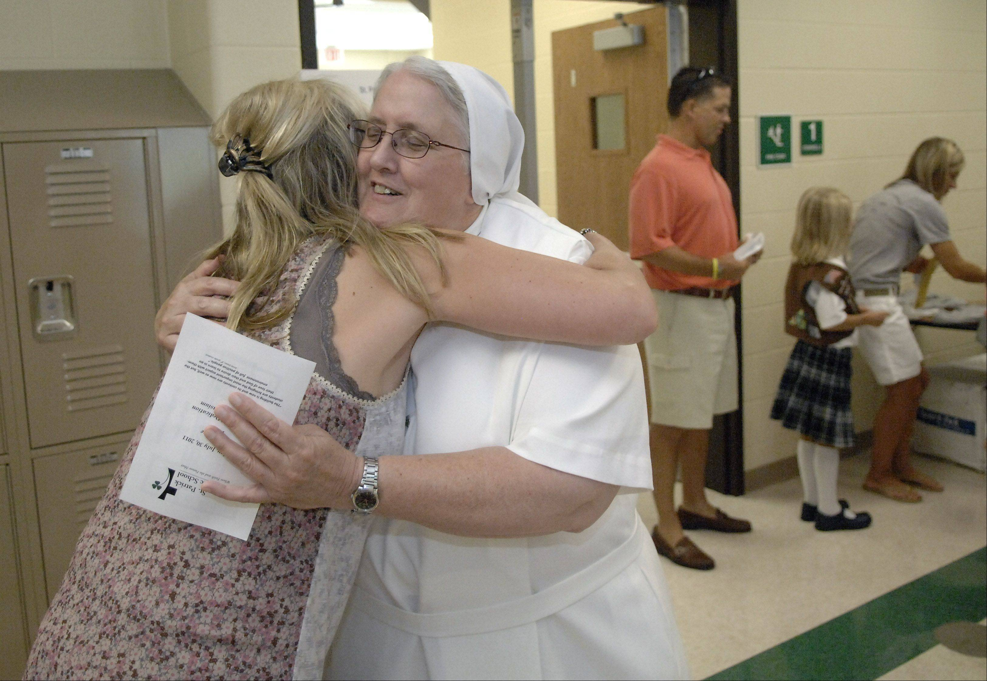 Assistant Principal Sister Liz Ryan gets a hug from parent Kim Calabria of South Elgin at the open house for the new St. Patrick Catholic School on Crane Road in St. Charles on Saturday. Calabria has three boys attending the school. A blessing and dedication followed later in the morning by Bishop Thomas G. Doran of the Rockford Diocese.