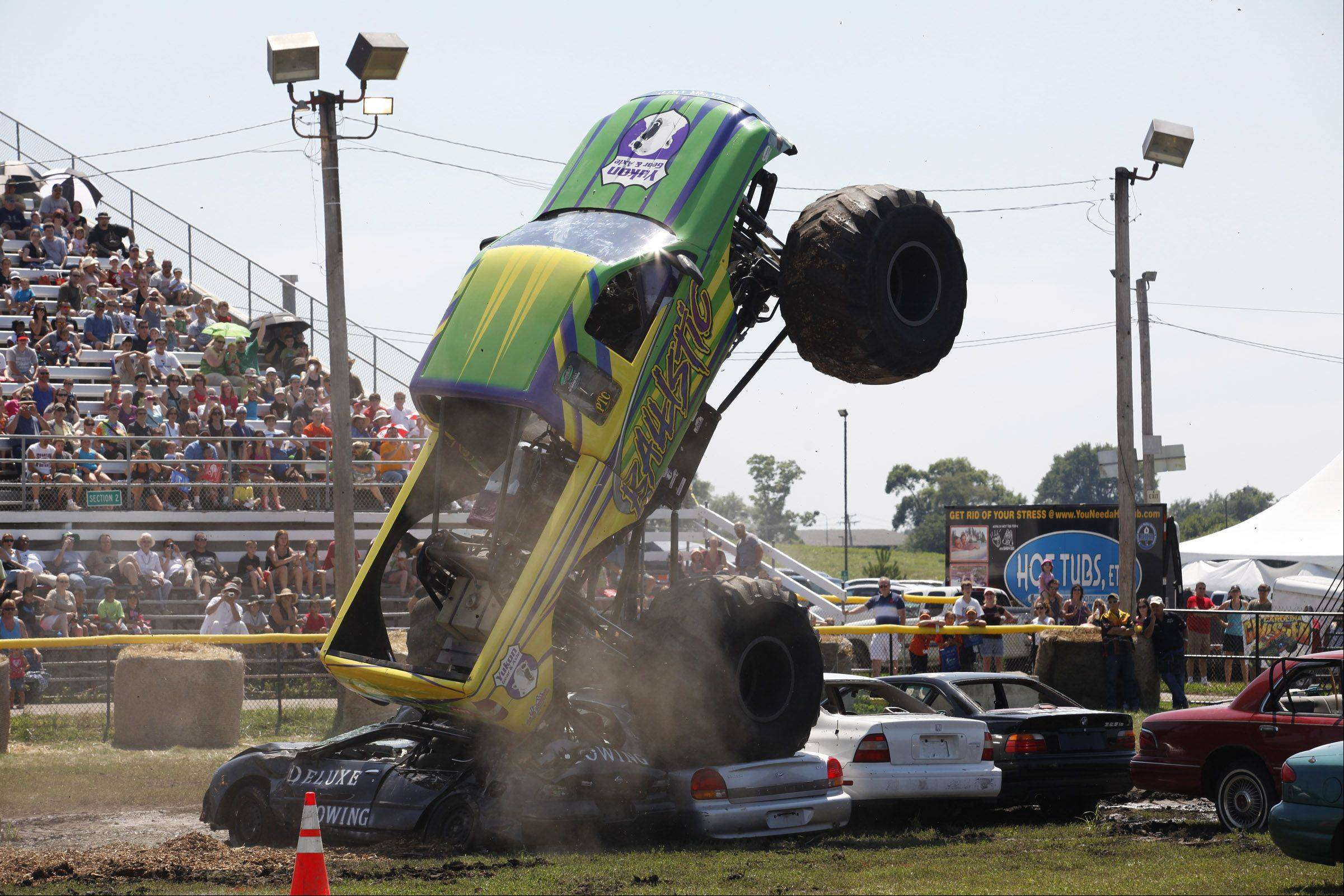 "Monster truck ""Ballistic"" wheelies goes over a line of cars Saturday as the crowd watches from the grandstands at the DuPage County Fair in Wheaton."