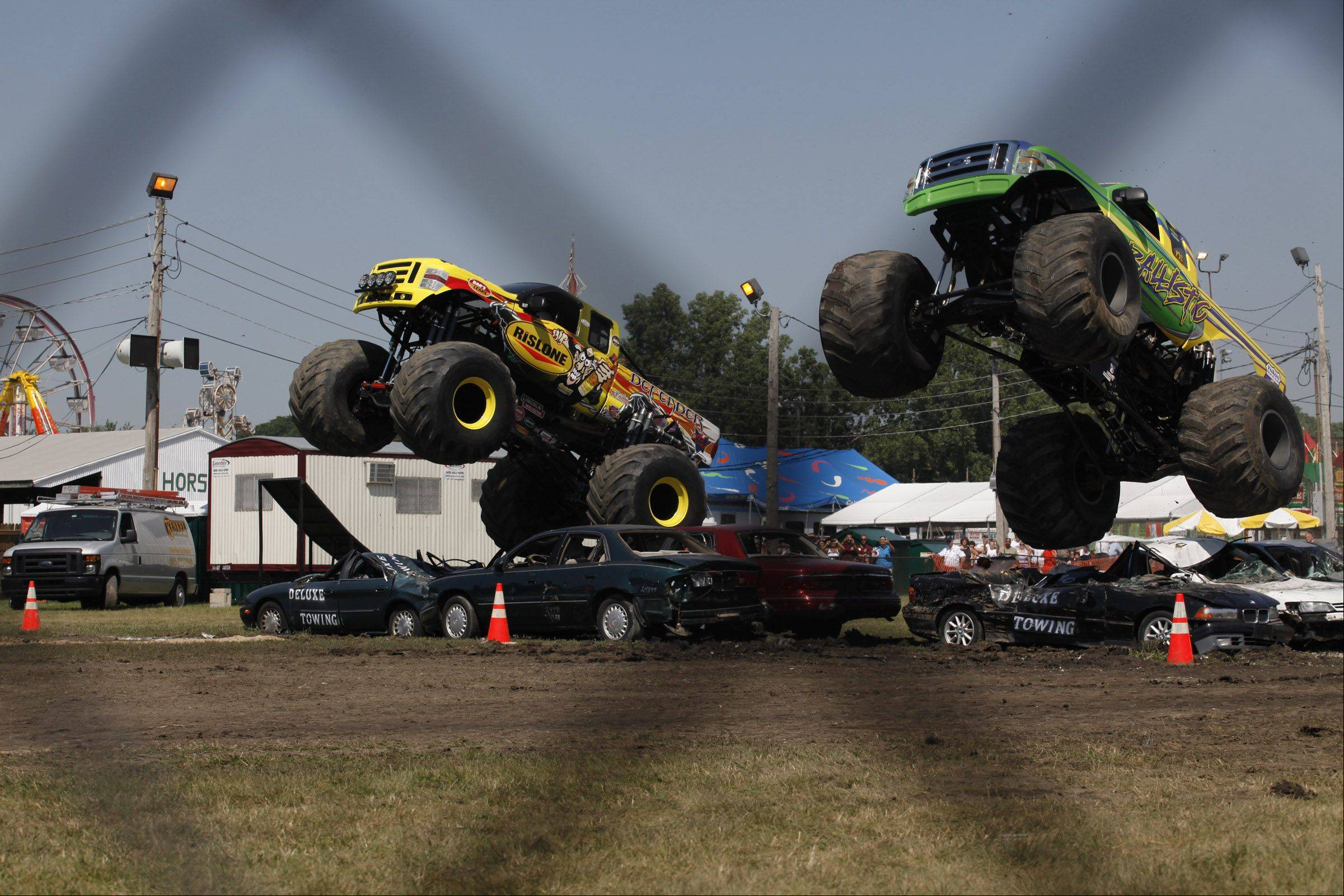 Rick Majewski/rmajewski@dailyherald.comDefender and Ballistic go head to head in a race over some cars in the DuPage County Fairs monster truck show in Wheaton. Saturday July 30th 2011.