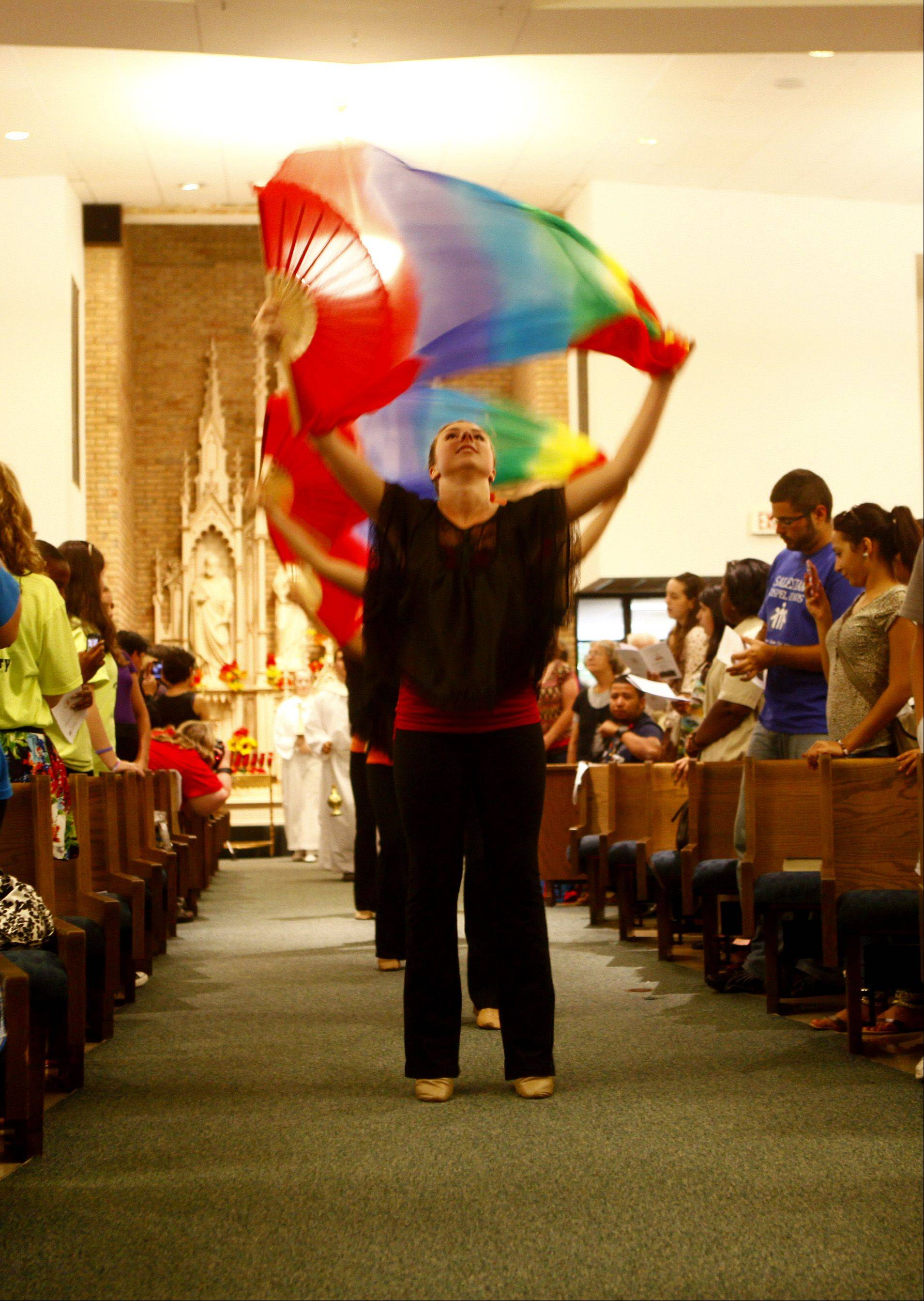 Ella Smoot, 18, of Kildeer participates in the processional dance at the beginning of a special Mass Friday night at St. Mary Parish in Buffalo Grove.