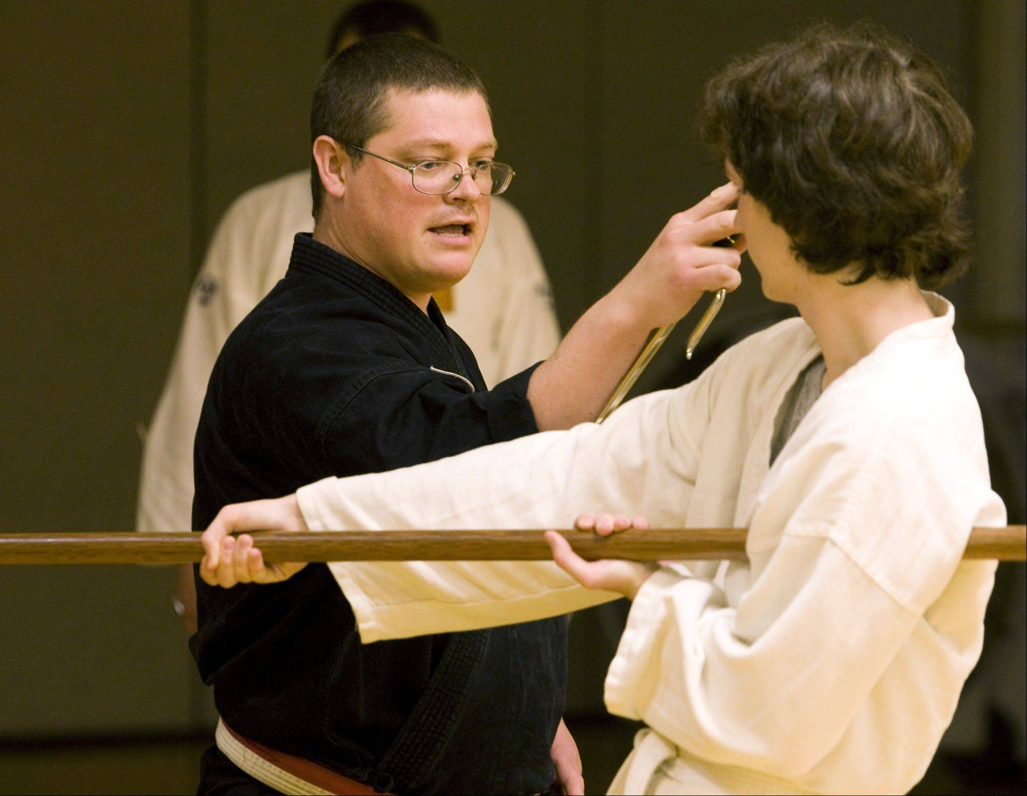 Kevin Hughes, a martial arts instructor at the Decatur YMCA, works with 16-year-old Keith Chapman during a weapons training portion of a class. Hughes specializes in teaching the power of self-control.