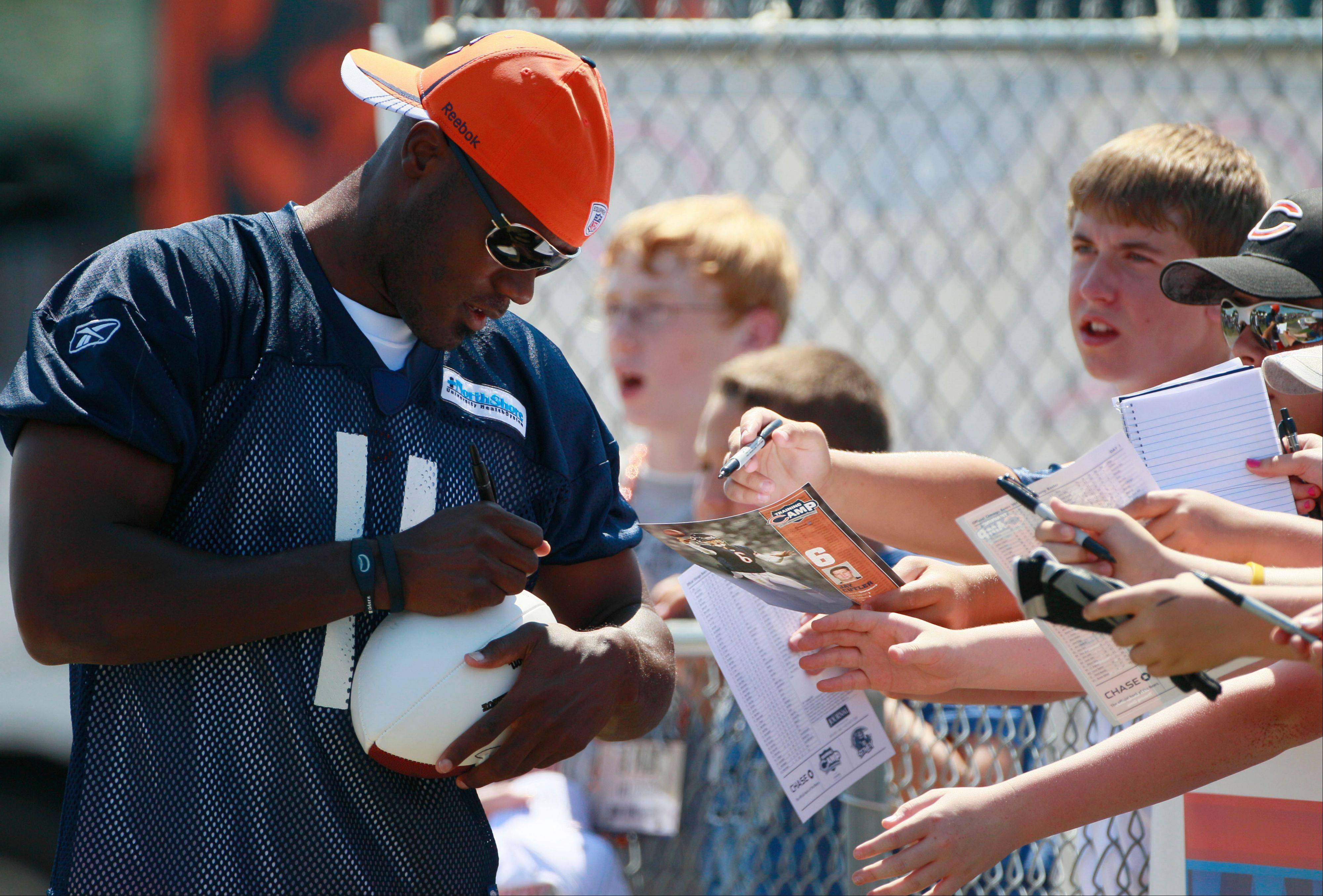 Wide receiver Roy Williams signs autographs as he walks on the field during the first day of training camp Saturday.