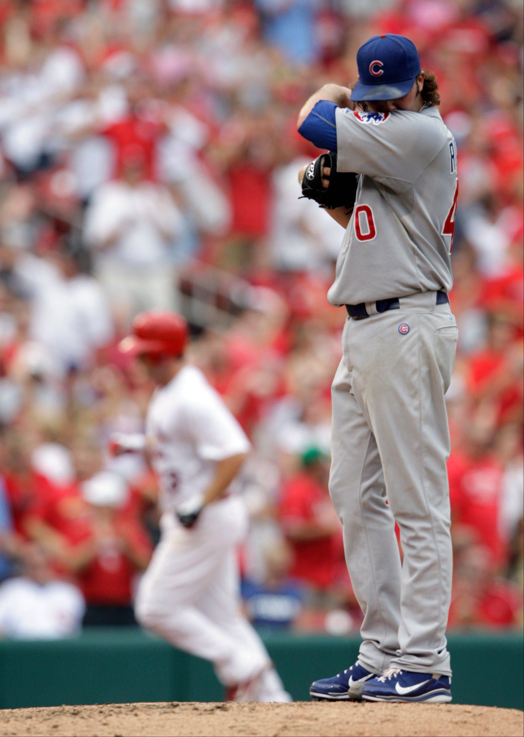 Cubs relief pitcher James Russell looks away as the Cardinals' David Freese circles the bases after hitting a 2-run homer Saturday.