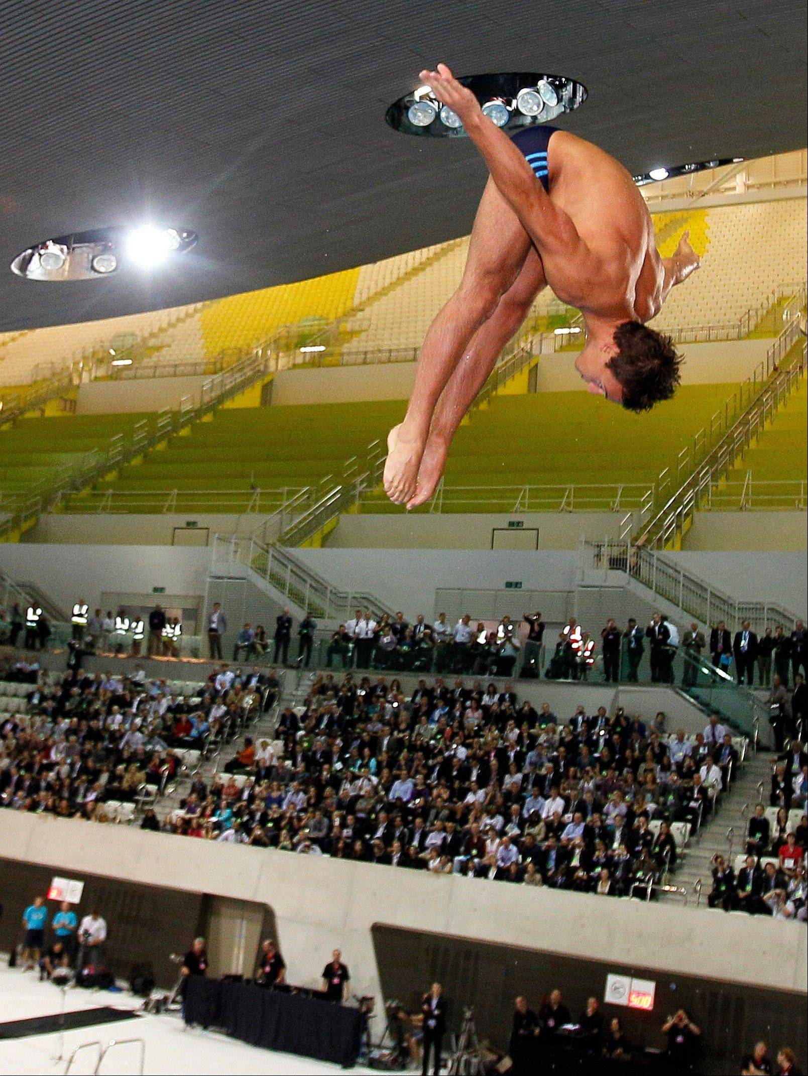 British Olympian Tom Daley performs a dive into the new aquatic centre dive pool at the one-year-to-go ceremony Wednesday in London.