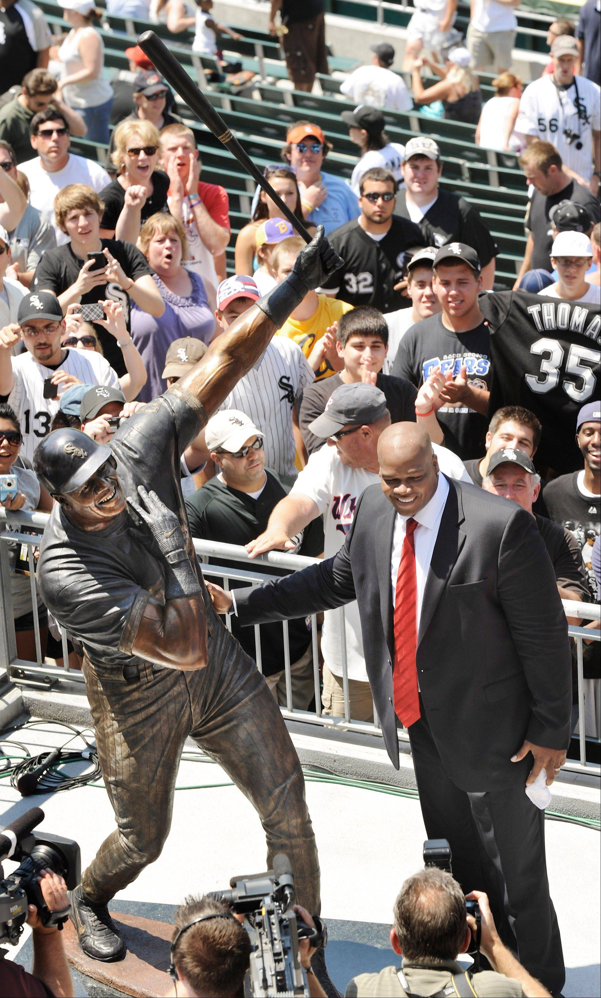 Frank Thomas, considered the best hitter in White Sox history, poses with a statue of himself during an unveiling ceremony Sunday at U.S. Cellular Field.