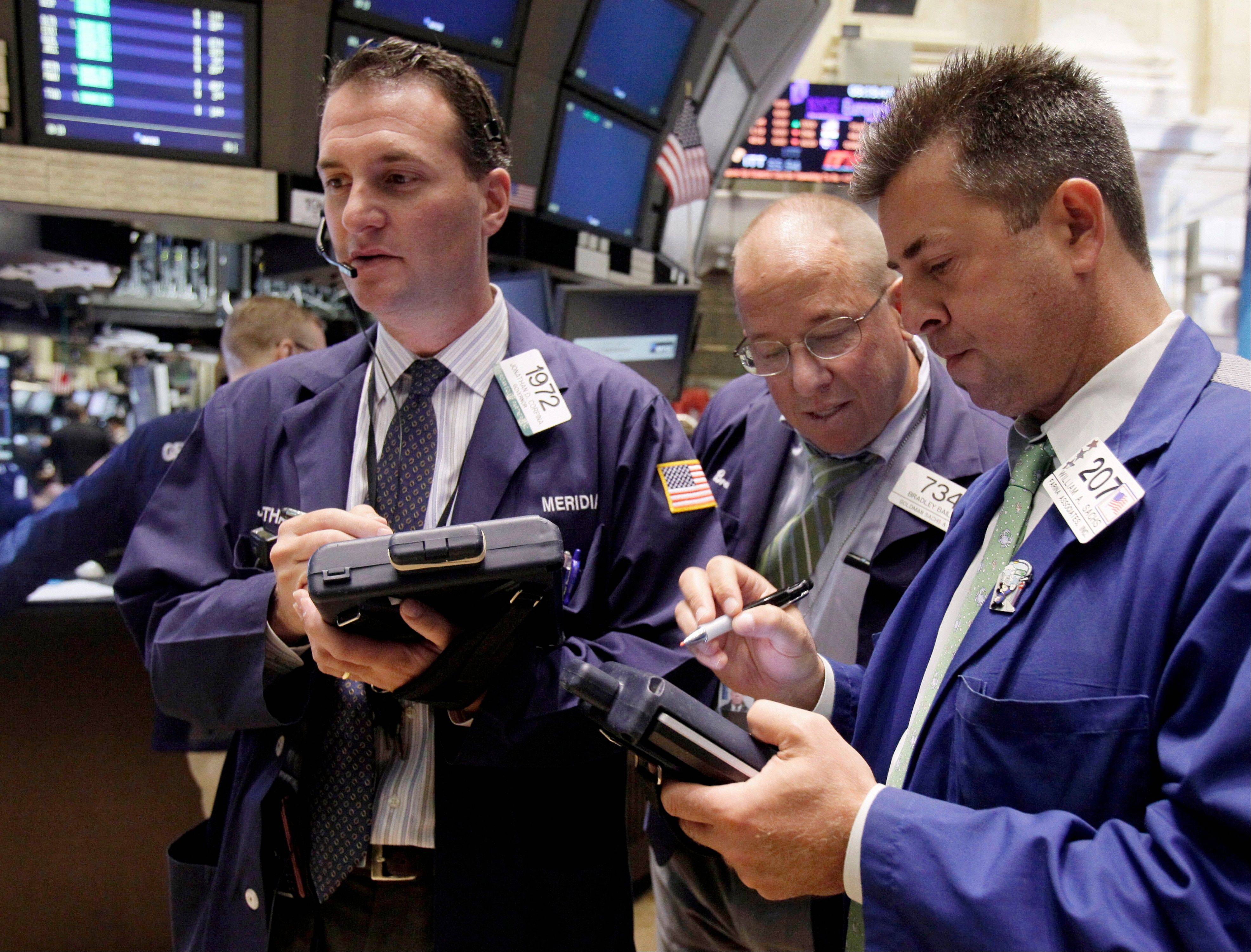 Traders Jonathan Corpina, from left, Bradley Bailey, and William Sachs work on the floor of the New York Stock Exchange. The political brinkmanship over raising the U.S. debt ceiling continued to weigh on markets Thursday, and the Dow Jones industrial average fell 62.44 points to close at 12,240.11.