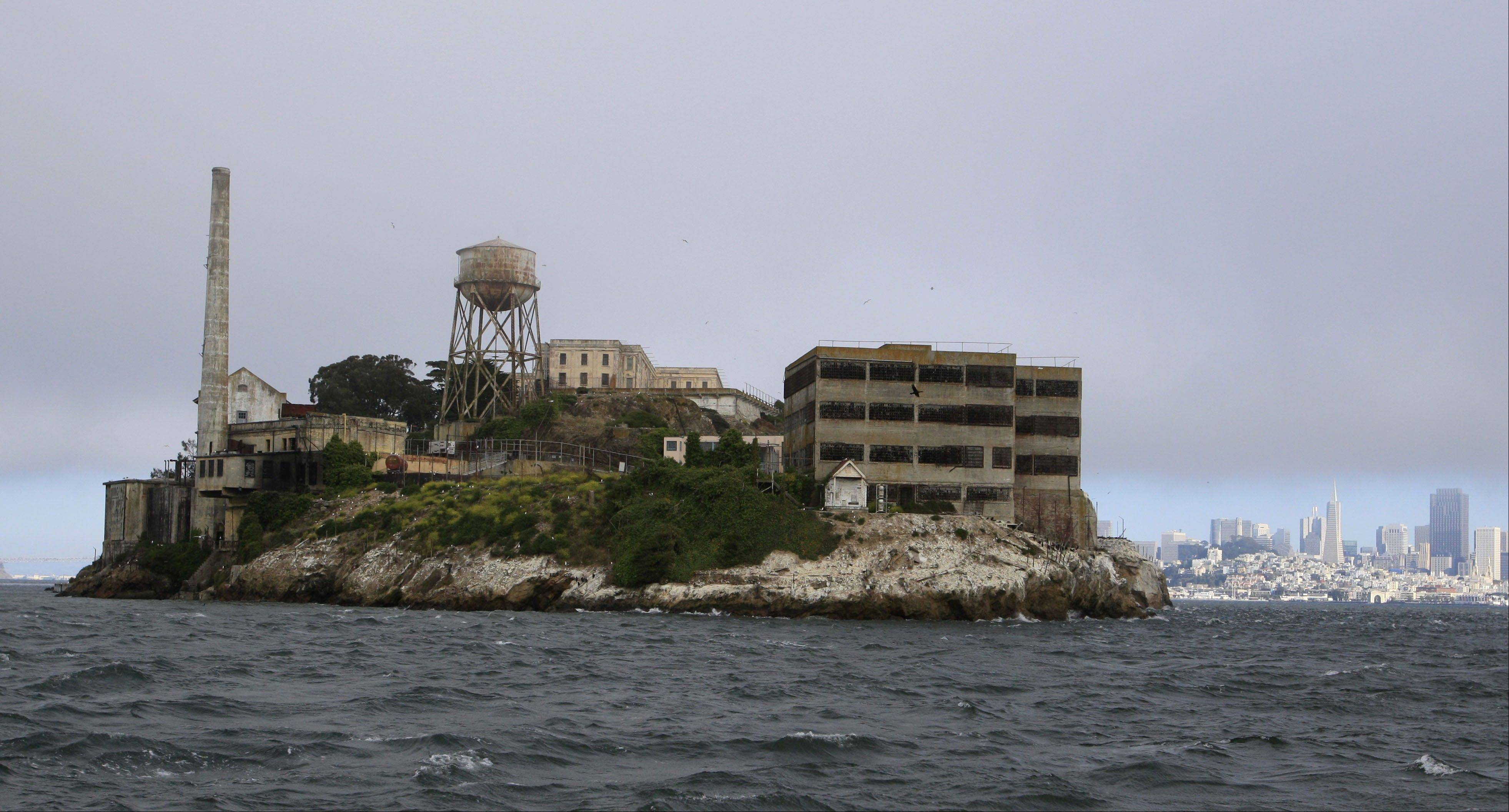 From a tour boat, visitors get a rare view of the west side of Alcatraz Island before taking the night tour of the former prison in San Francisco.