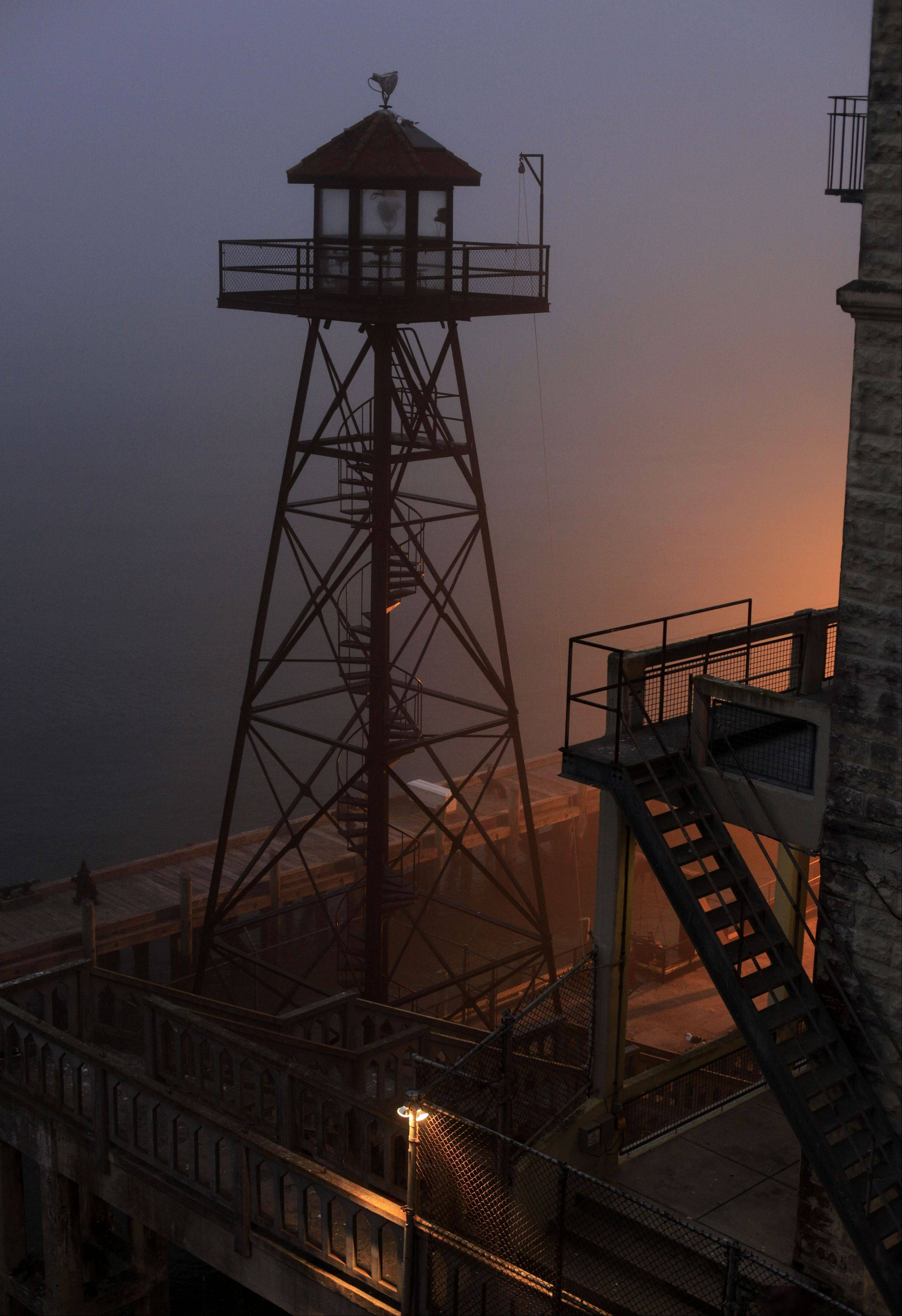 A guard tower stands near the dock during a night tour on Alcatraz Island. At dusk the island prison that housed some of the nation's most notorious criminals, including James Whitey Bulger and Al Capone, is often covered in fog, and the lamps on the grounds emit a ghostly glow.