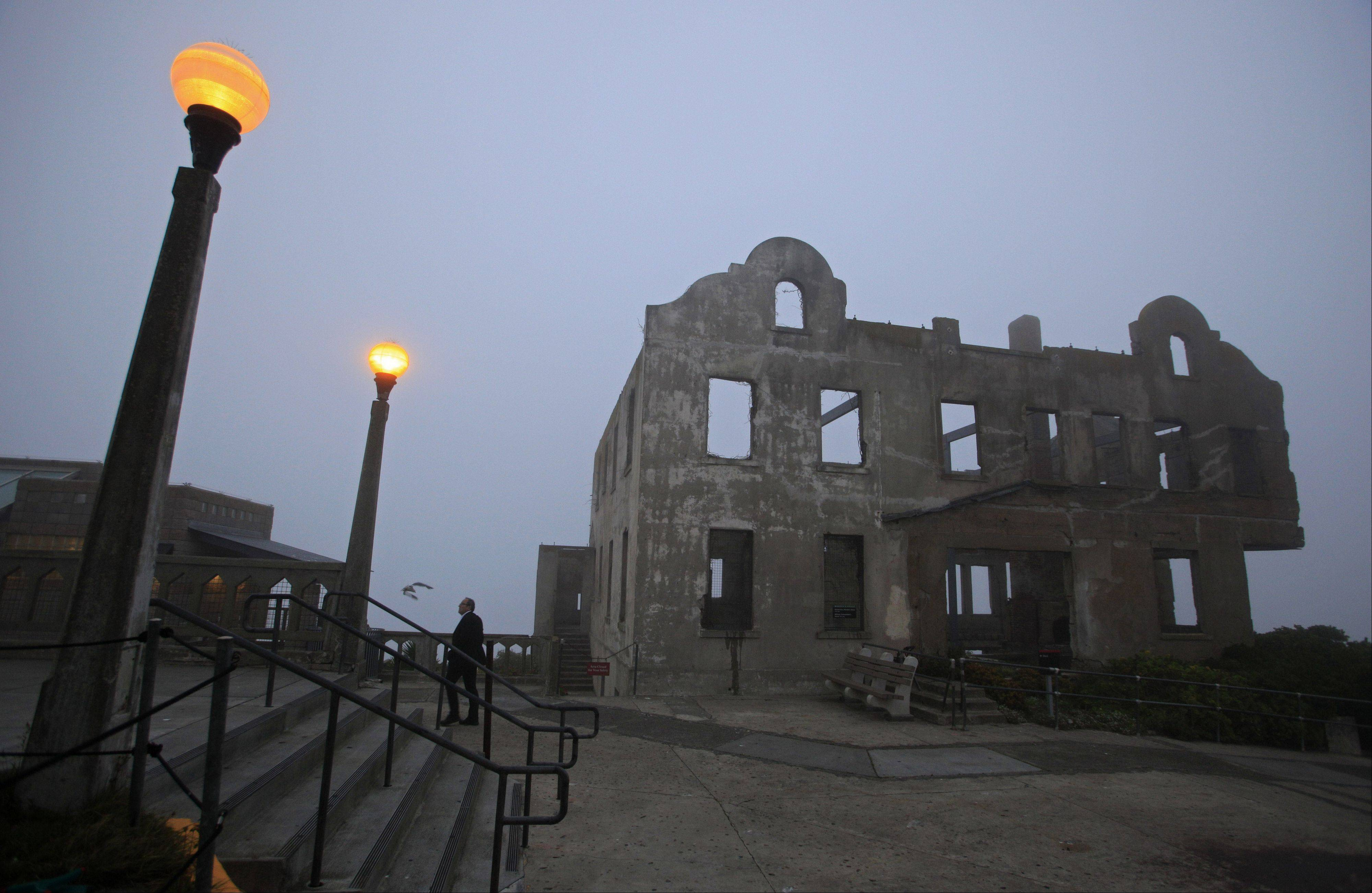 A man walks past the remains of the warden's house during a night tour of Alcatraz.