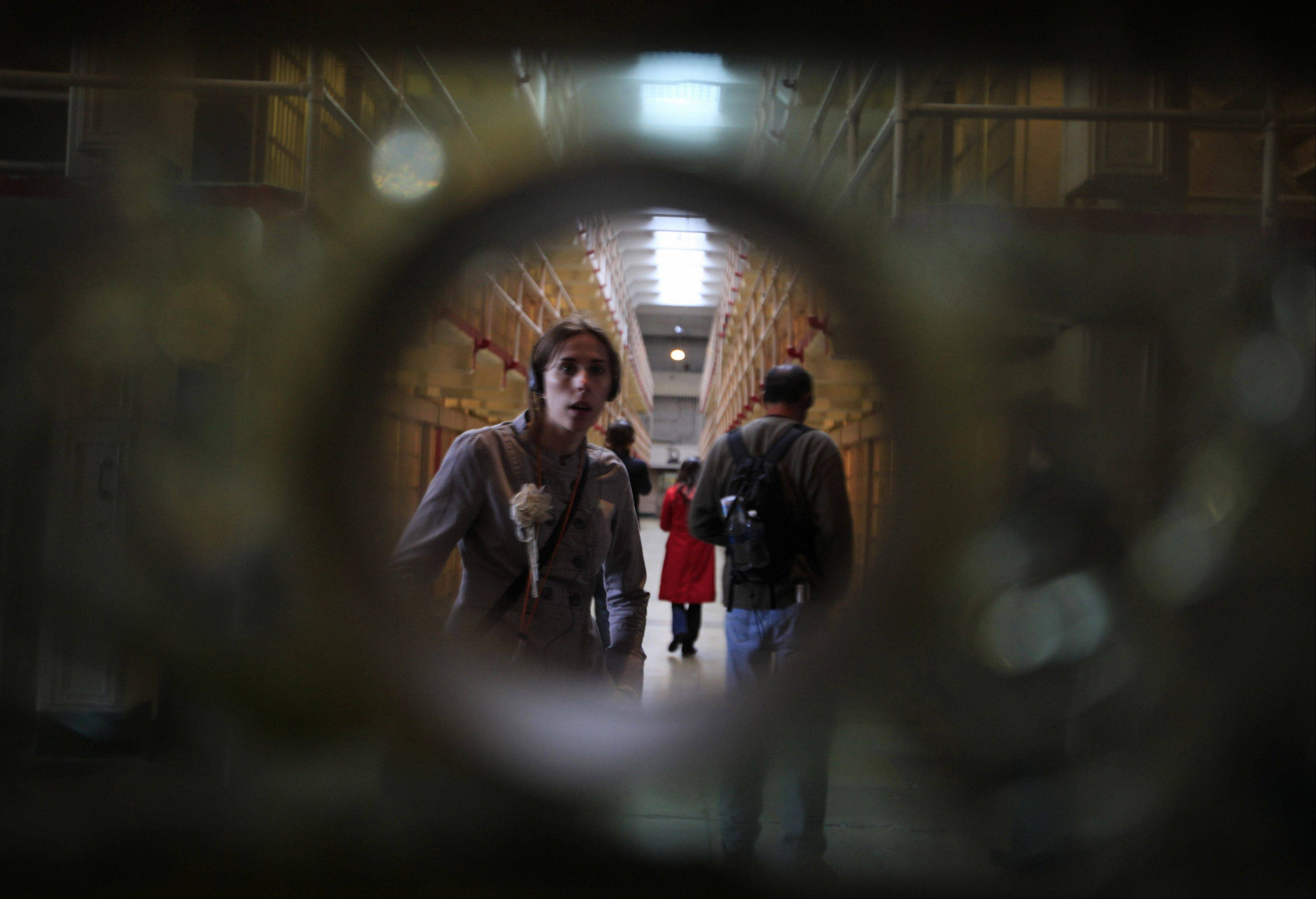 A woman looks through a hole and bulletproof glass into a visitation area. Most of the more than 1 million tourists who visit the famous former prison never get to experience Alcatraz at night or see its spooky, decrepit hospital.