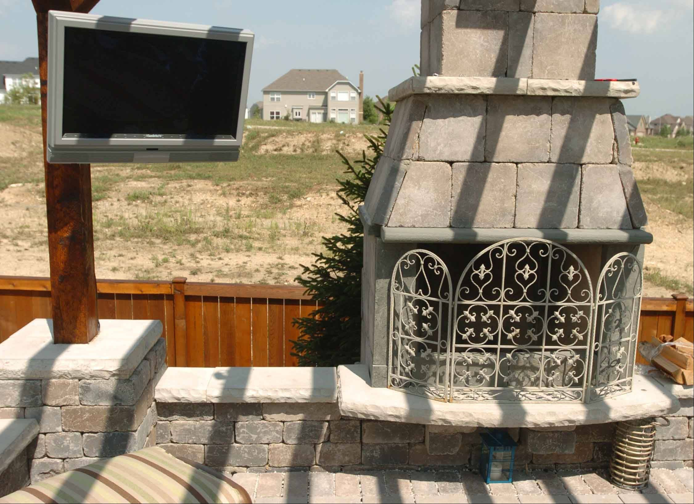 A special outdoor plasma television hangs by fireplace at the Jakovich home in Plainfield.