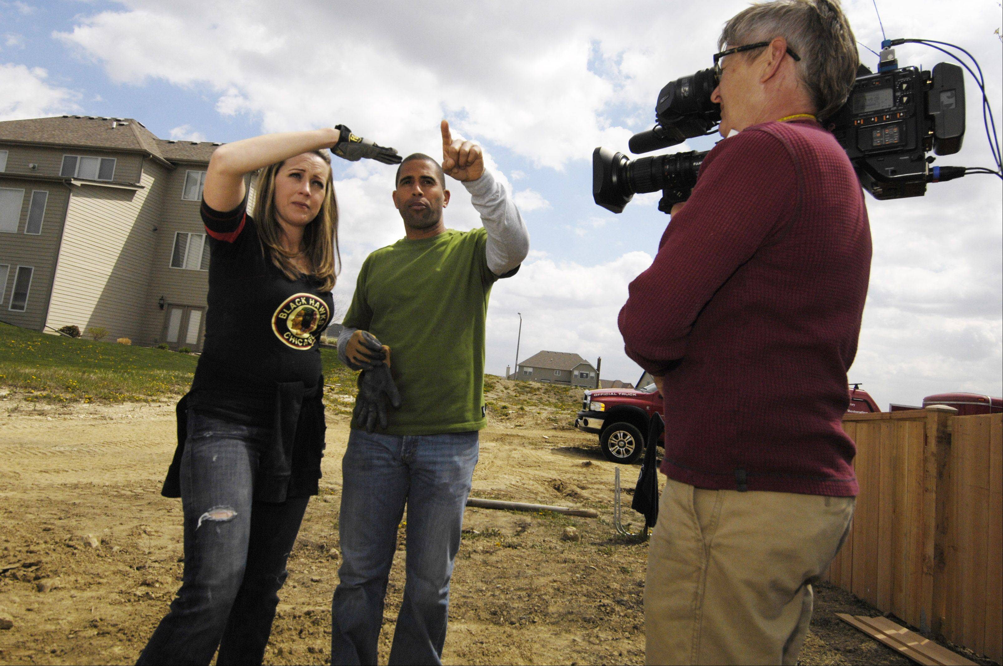 "Homeowner Amanda Jakovich talks with ""Yard Crashers"" host Ahmed Hassan during the filming of a show in Jakovich's Plainfield backyard."