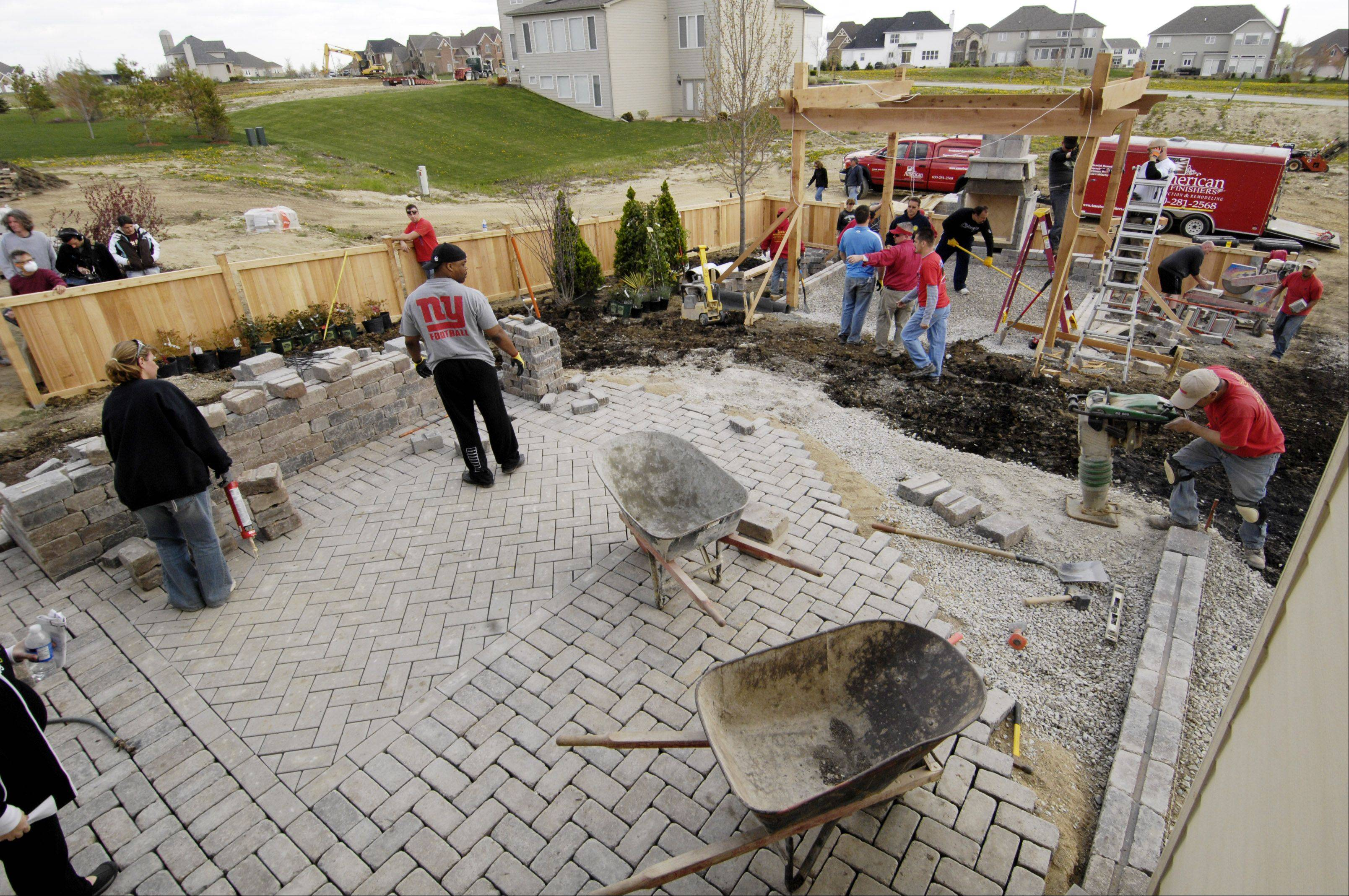 Volunteers and professionals worked together to get a huge patio built in the backyard of Jason and Amanda Jakovich in Plainfield.